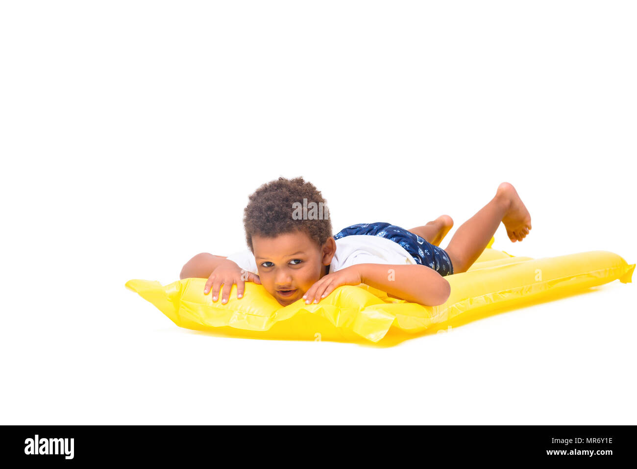 cute little african american boy lying on swimming mattress and looking at camera isolated on white - Stock Image