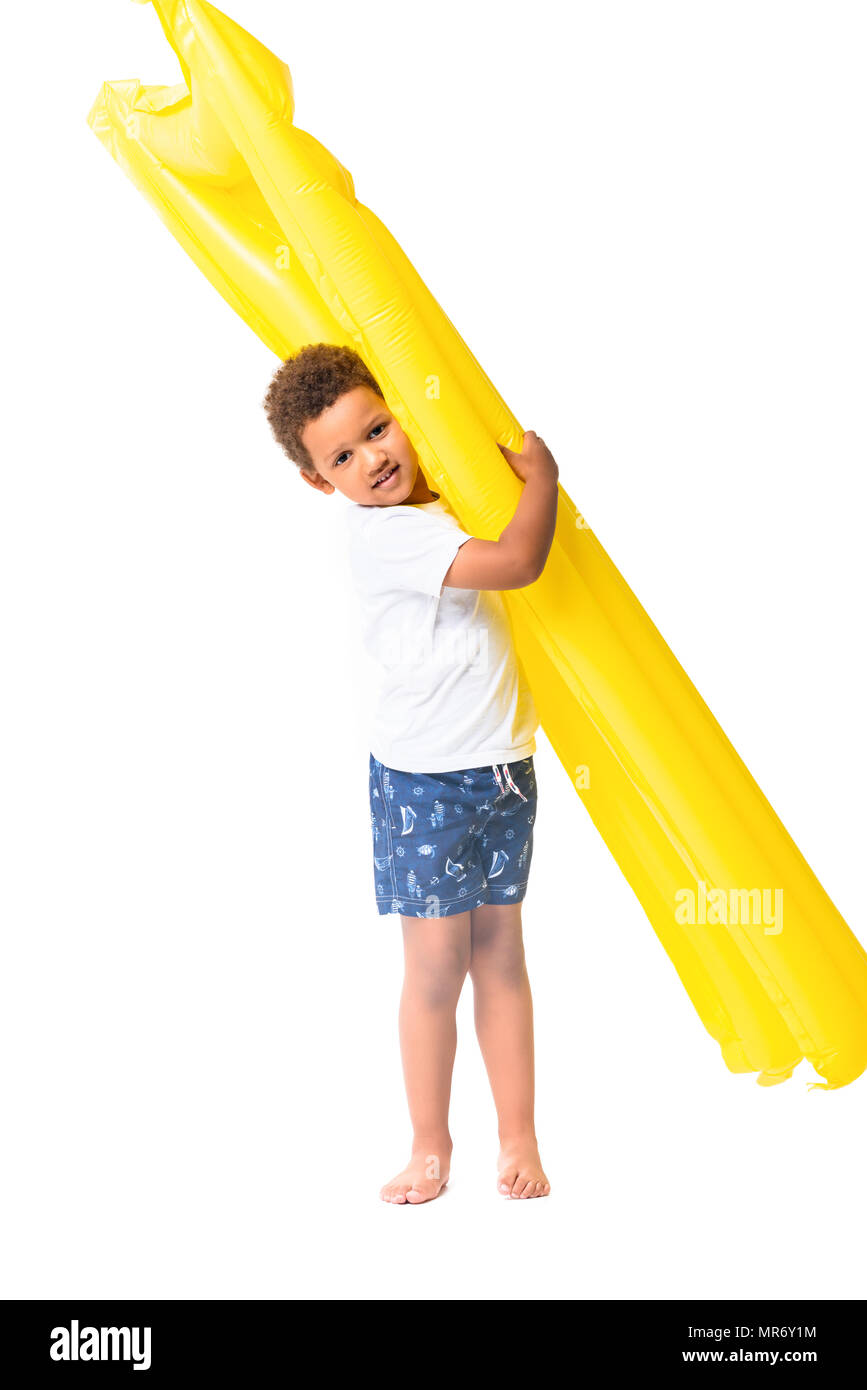 adorable african american boy holding swimming mattress and looking at camera isolated on white - Stock Image
