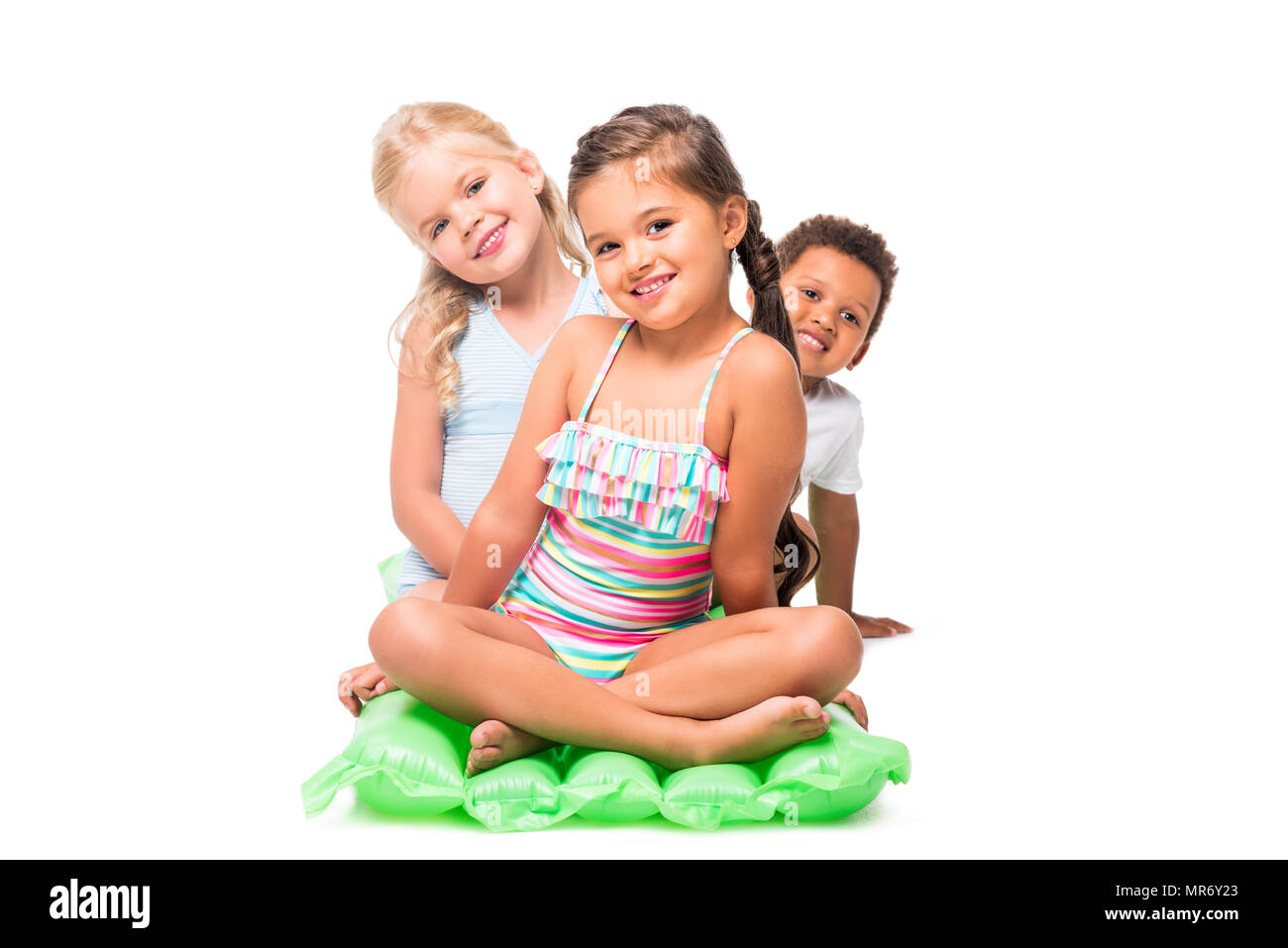 adorable multiethnic kids in swimwear sitting on swimming mattress and smiling at camera - Stock Image