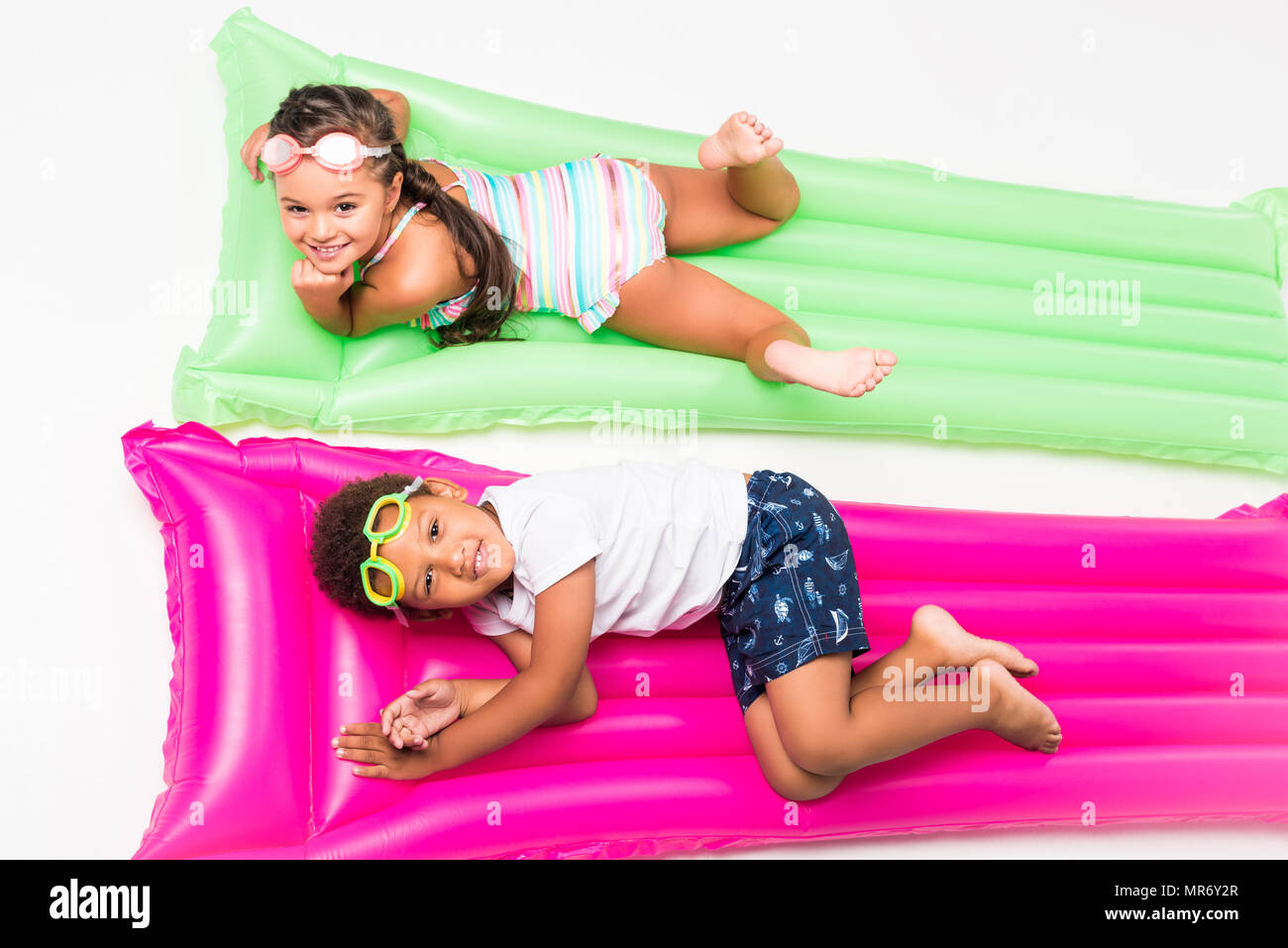 top view of cute multiethnic kids in swimwear lying on swimming mattresses and smiling at camera - Stock Image