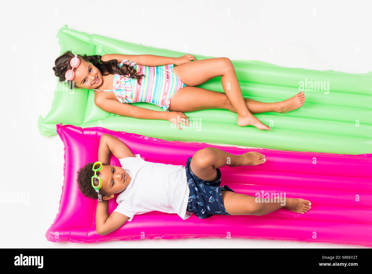 top view of cute multiethnic kids in swimwear lying on swimming mattresses isolated on white - Stock Image