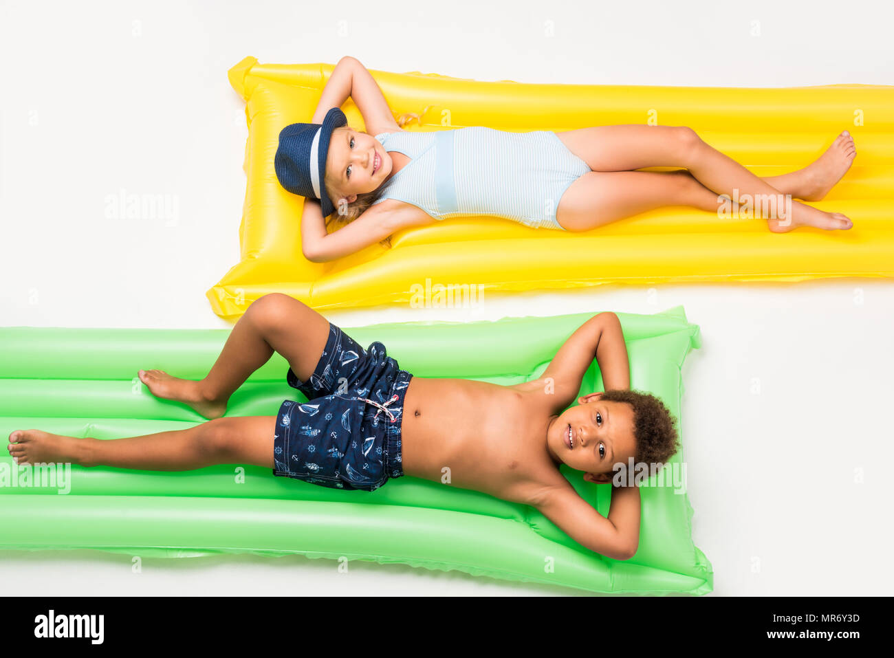 adorable multiethnic kids in swimwear lying on swimming mattresses isolated on white - Stock Image