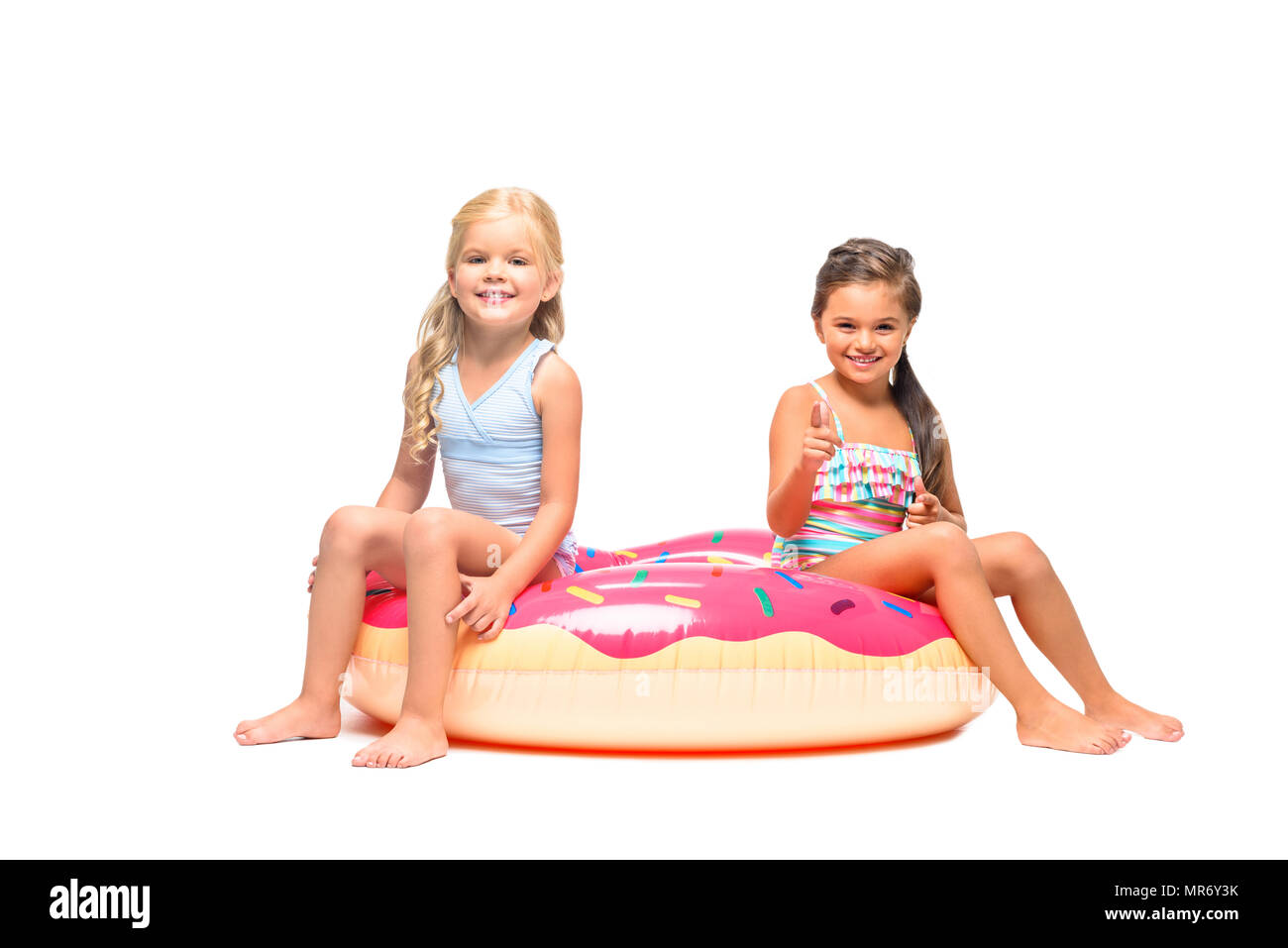 0a88f09788 adorable little girls in swimsuits sitting on swim tube and smiling at  camera isolated on white