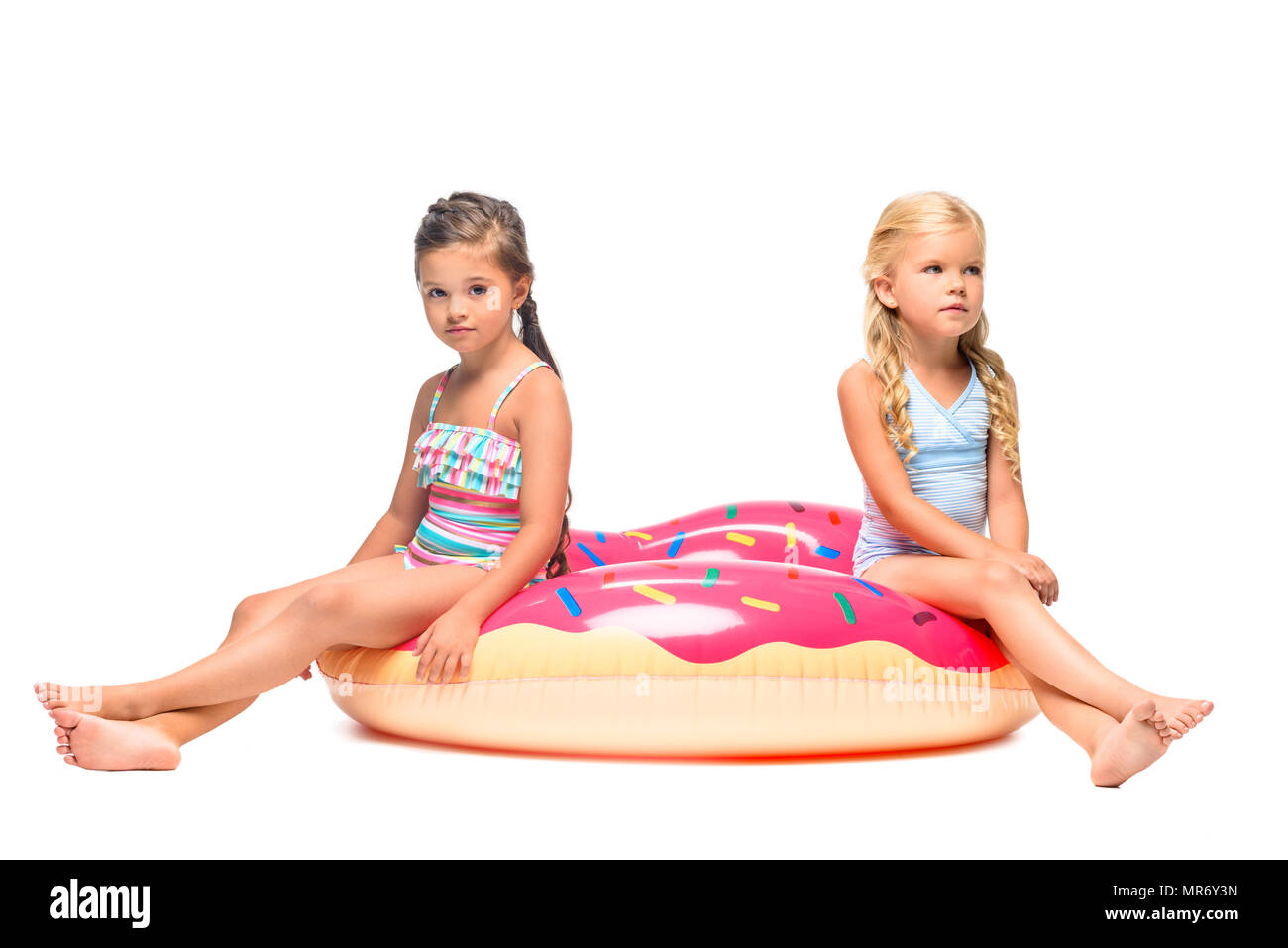 2a7600c581233 cute little girls in swimsuits sitting on water donut isolated on white -  Stock Image