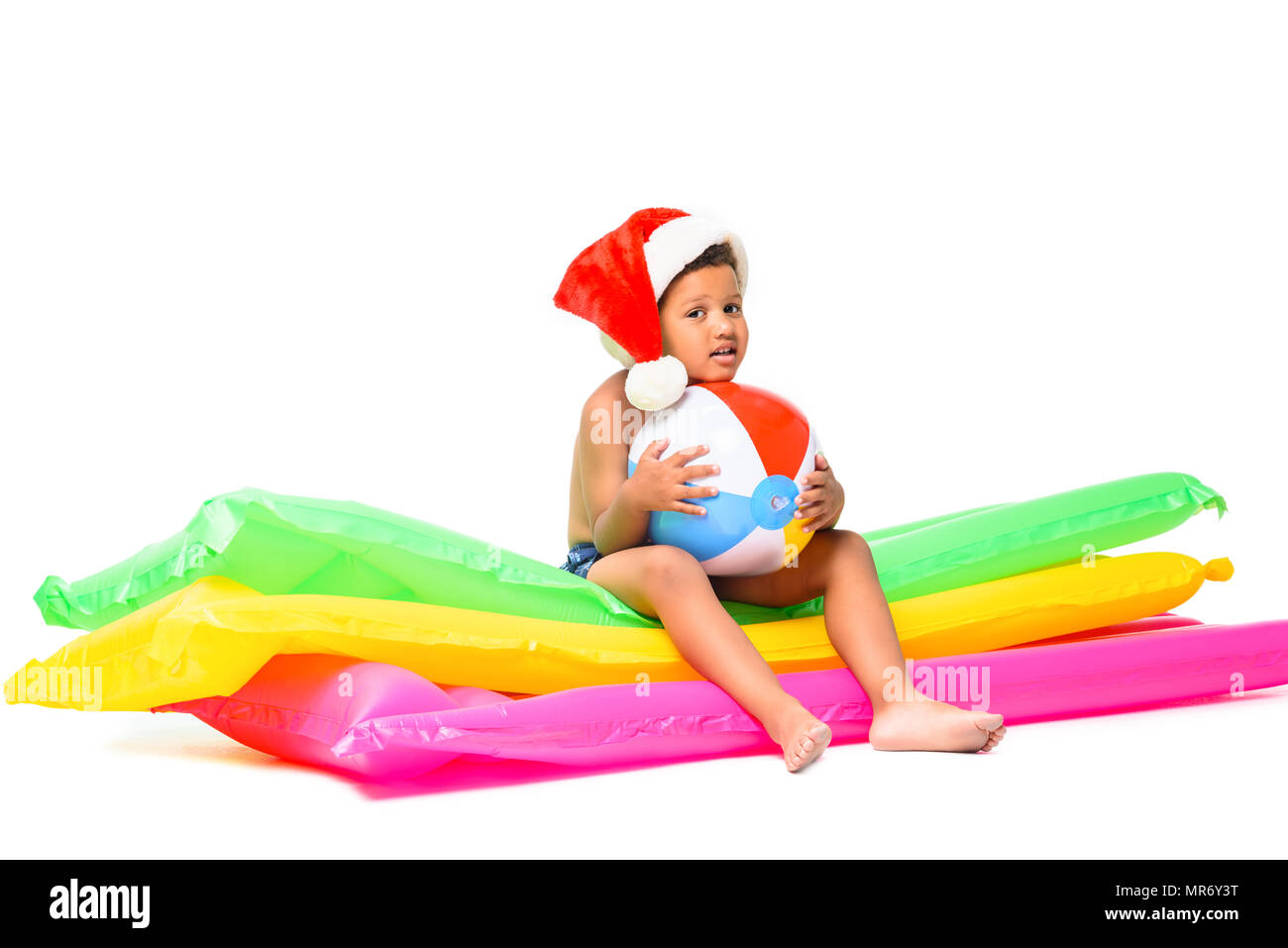 cute african american boy in santa hat holding ball while sitting on swimming mattresses - Stock Image