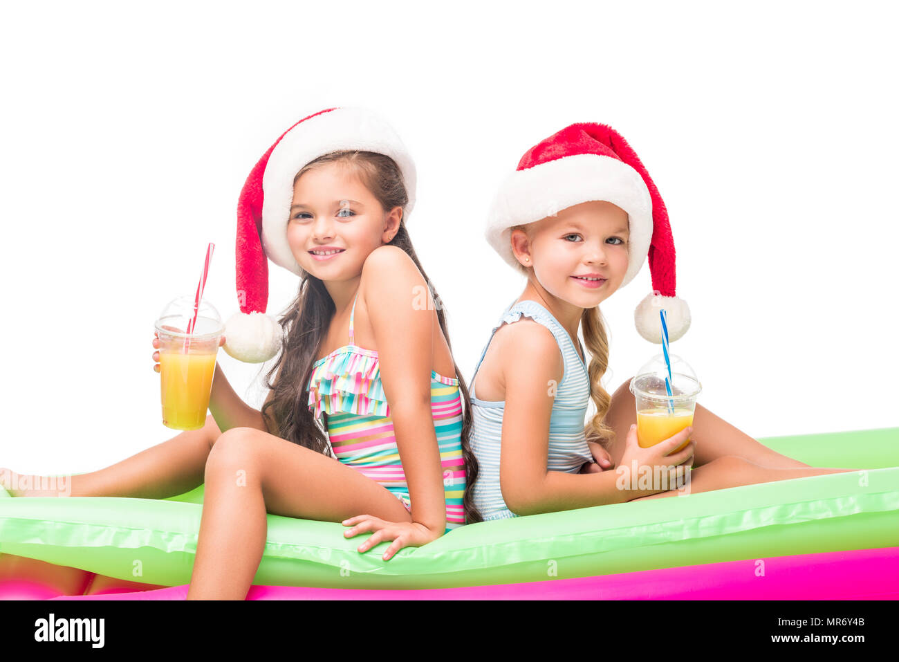 d65e812609896 adorable little girls in santa hats drinking orange juice while sitting on  swimming mattresses - Stock