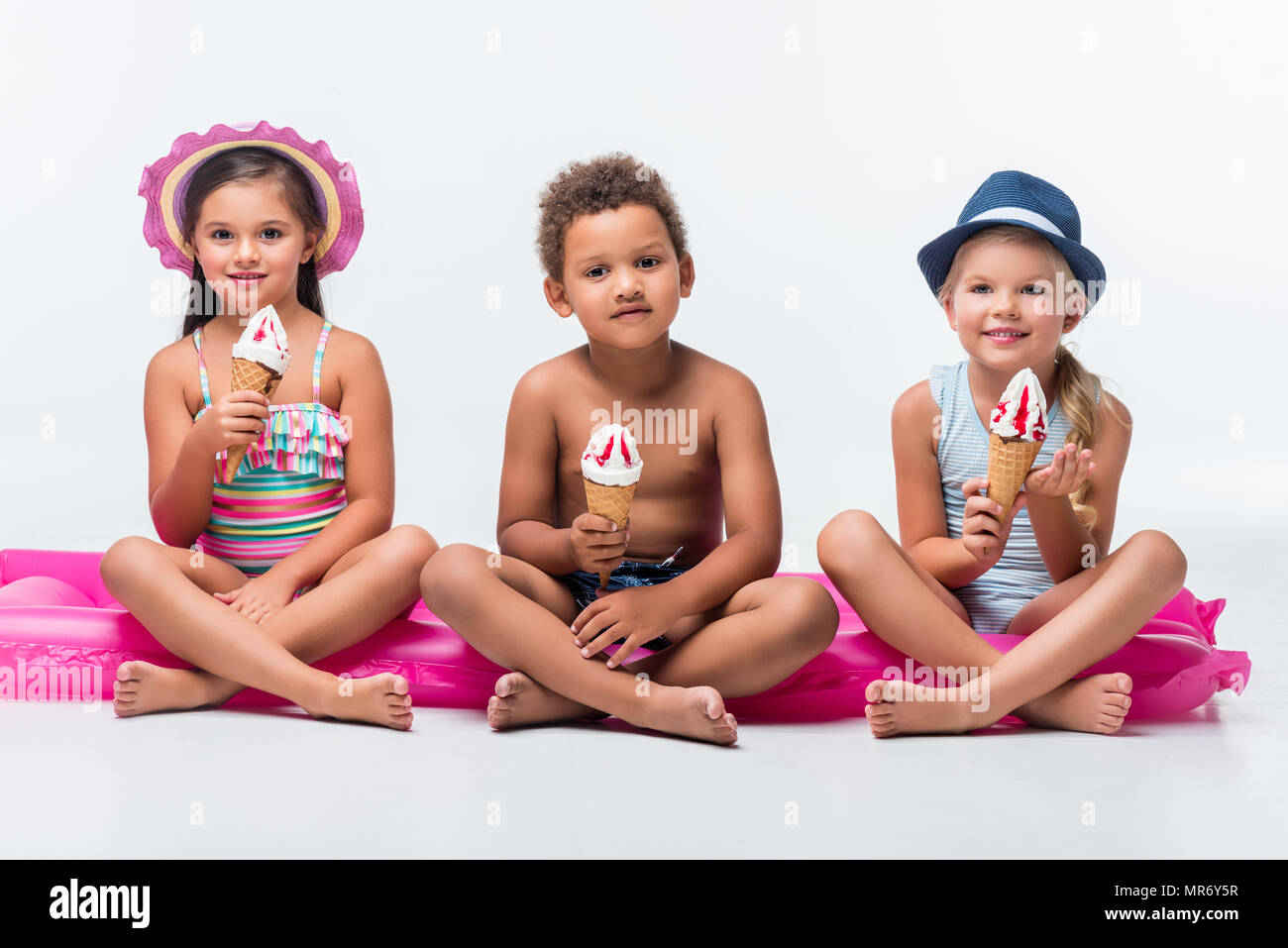 adorable multiethnic kids in swimwear eating ice cream while sitting on swimming mattress - Stock Image