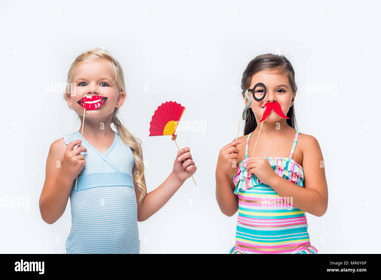 080a056886530 adorable little girls in swimsuits holding party sticks and looking at camera  isolated on white -