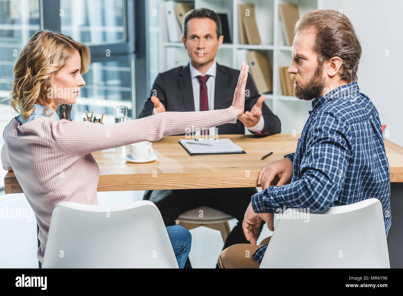 side view of couple arguing at workplace in lawyer office - Stock Image