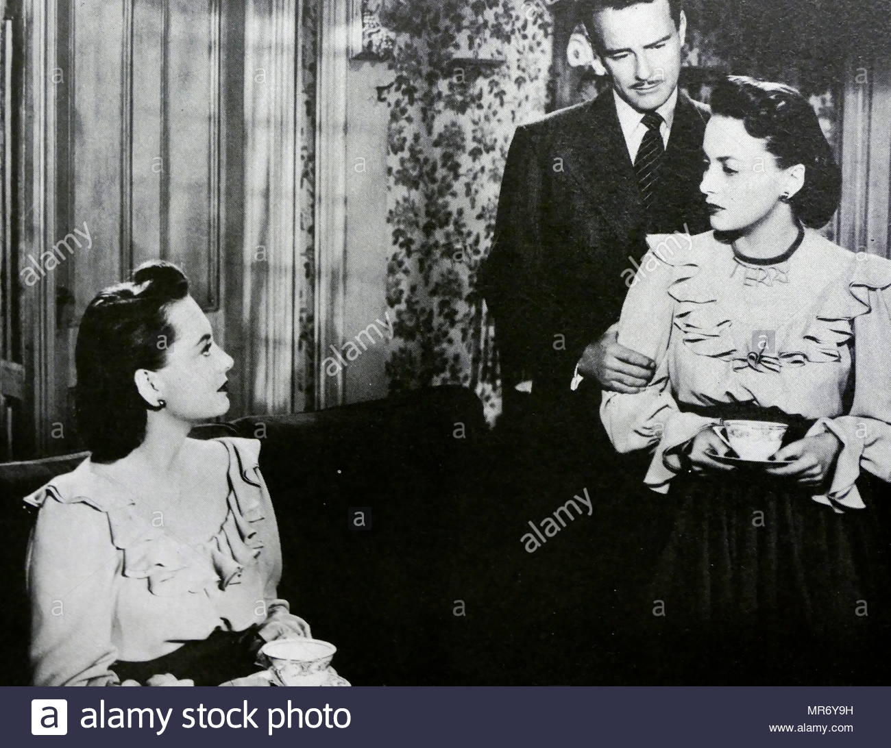 The Dark Mirror is a 1946 American film noir psychological thriller film directed by Robert Siodmak starring Olivia de Havilland as twins and Lew Ayres as their psychiatrist. - Stock Image