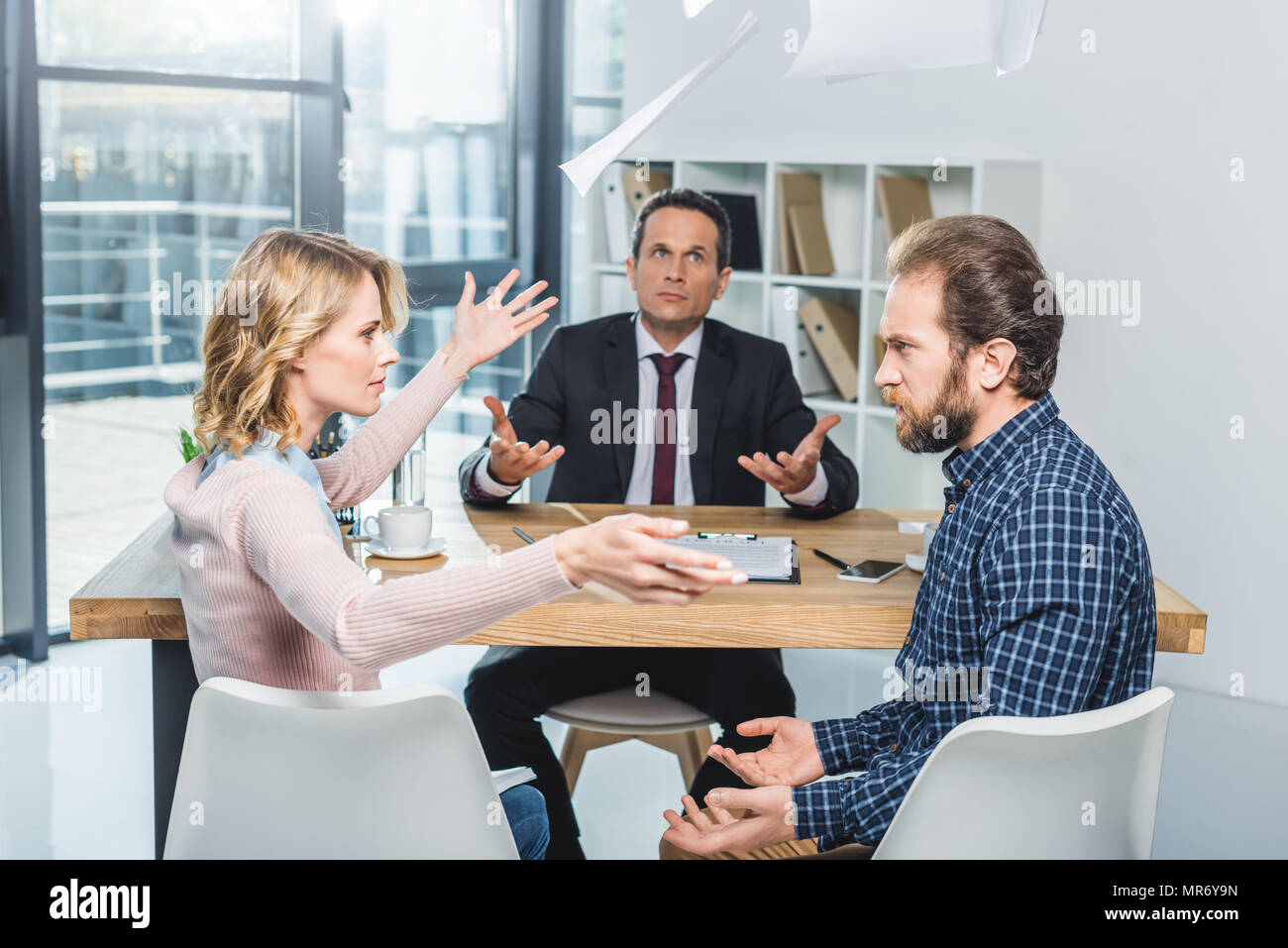 side view of couple having argument during meeting with lawyer in office - Stock Image