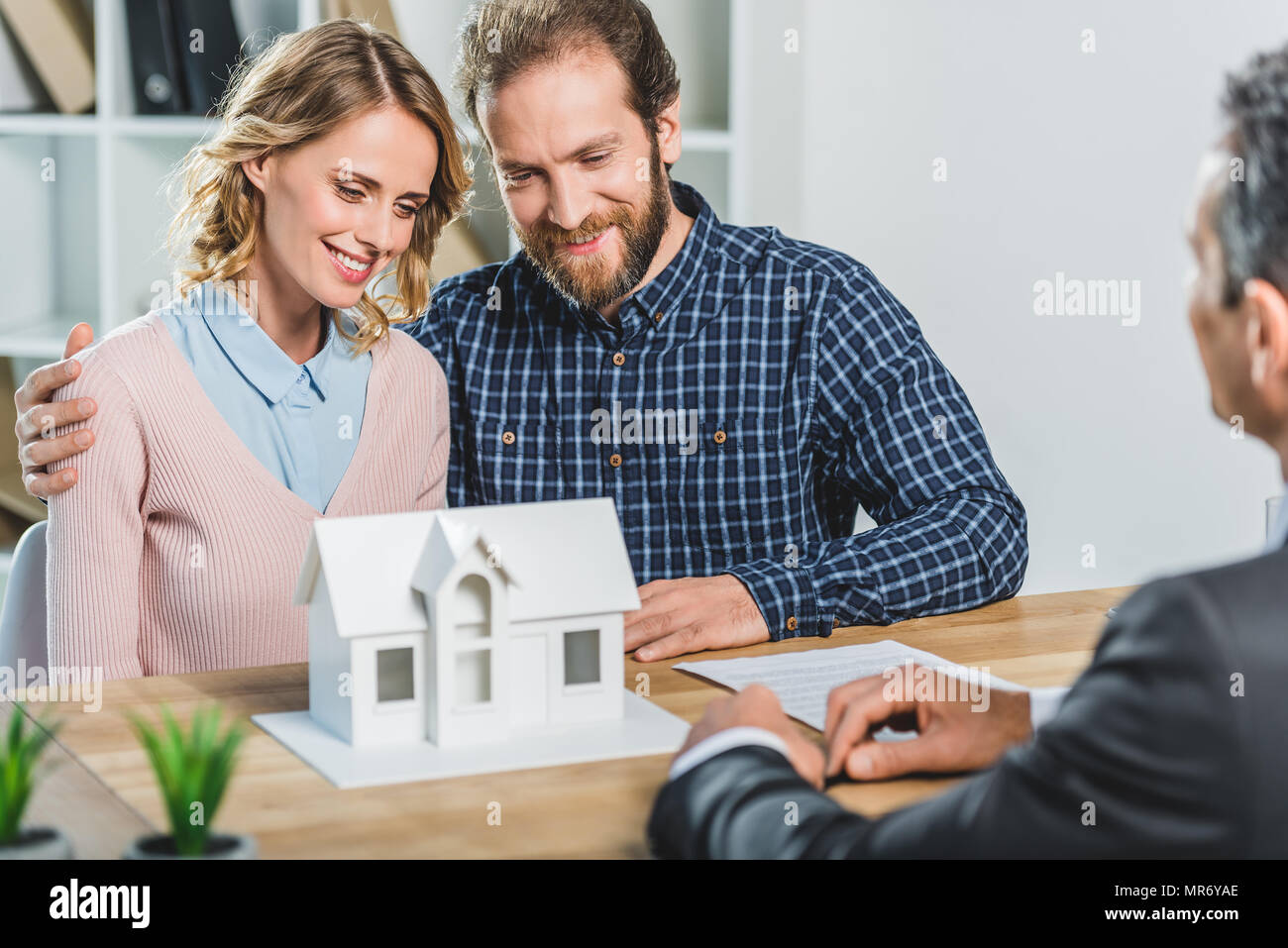 portrait of couple having meeting with realtor in real estate agency office - Stock Image