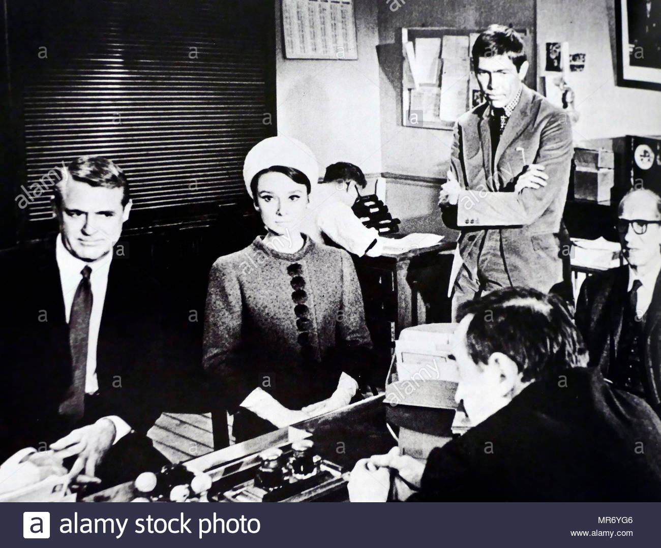 Charade; 1963 American romantic film, directed by Stanley Donen. Written by Peter Stone and Marc Behm, and starring Cary Grant and Audrey Hepburn. The cast also features James Coburn - Stock Image