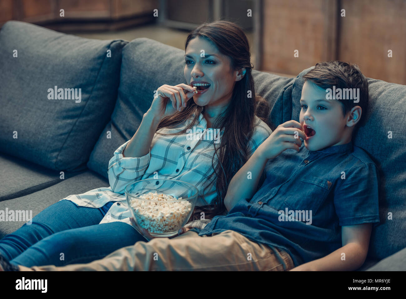 Little son and his young mother sitting on couch while watching tv and eating popcorn - Stock Image