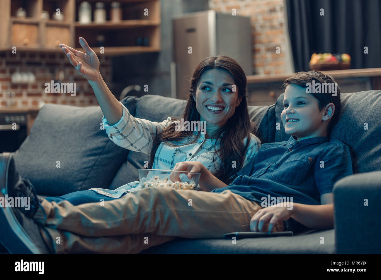 Little son and his young mother talking while watching tv on couch and eating popcorn - Stock Image