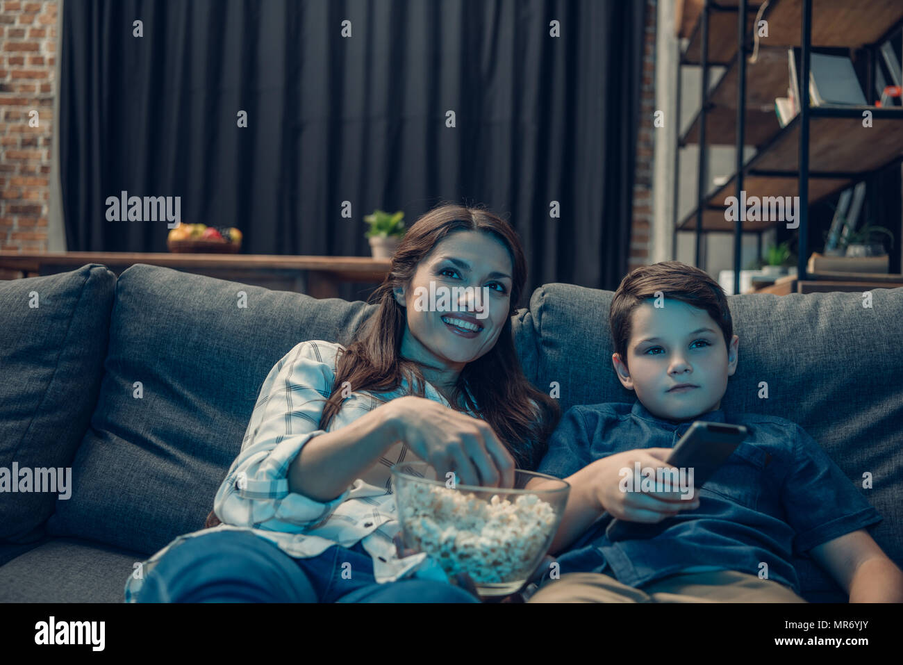 Little boy and his beautiful mother watching tv and eating popcorn - Stock Image