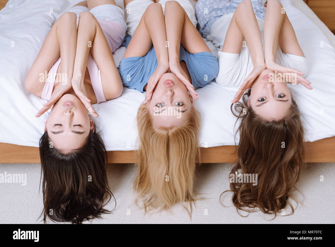 overhead view of multicultural friends grimacing and hanging down from bed - Stock Image