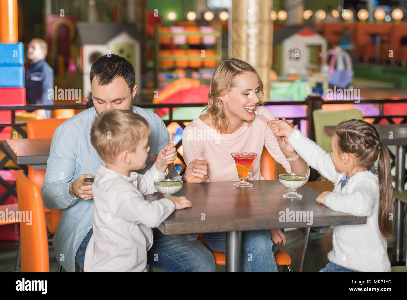 family with two children eating tasty desserts and father using smartphone in cafe - Stock Image