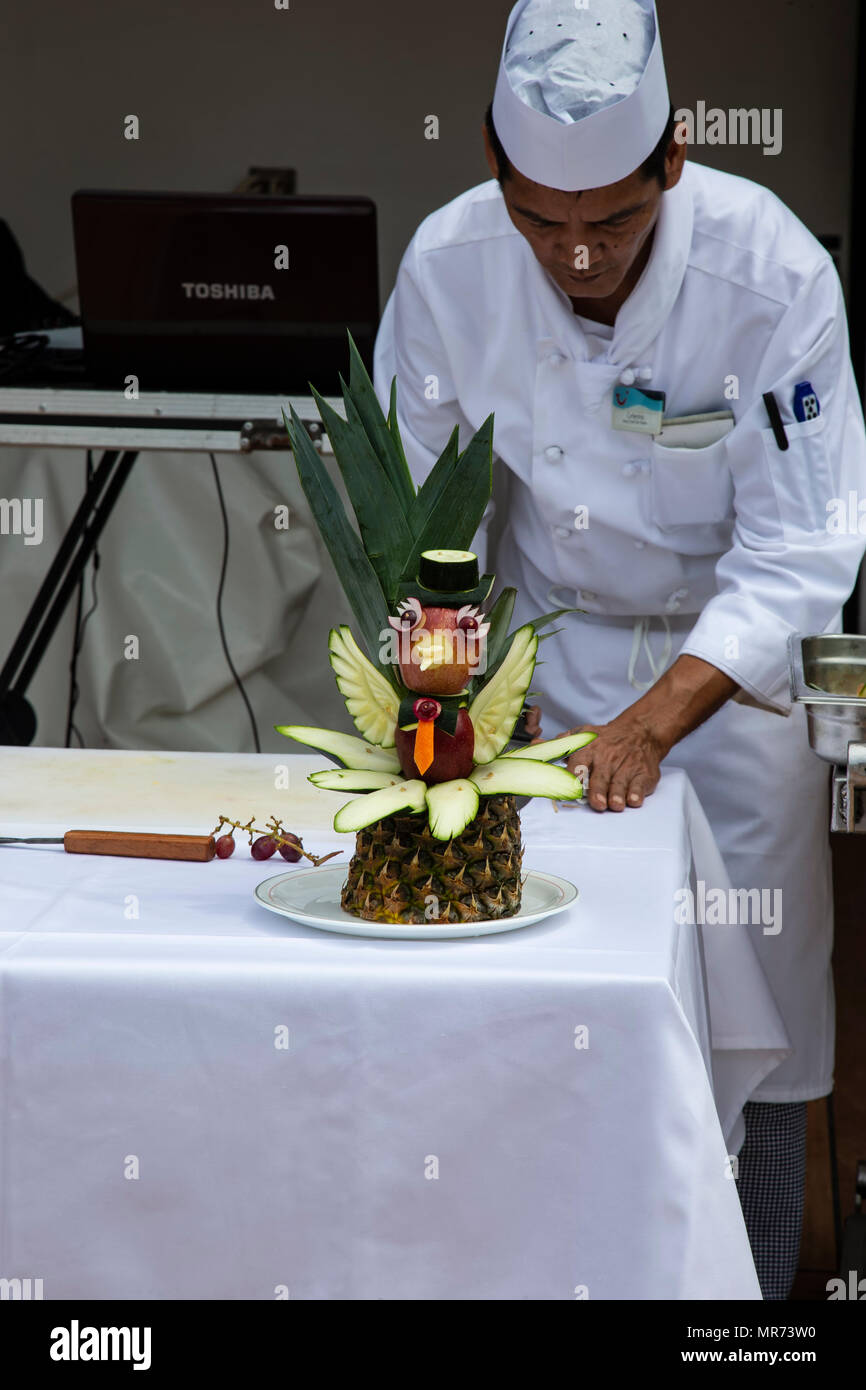 Chef on a cruise liner carving a stylised duck from assorted fruit and vegetables - Stock Image