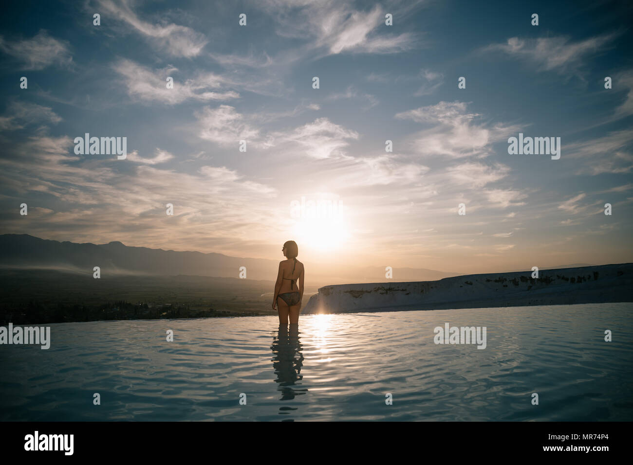back view of young woman standing in beautiful natural pool and looking at majestic landscape in pamukkale, turkey Stock Photo