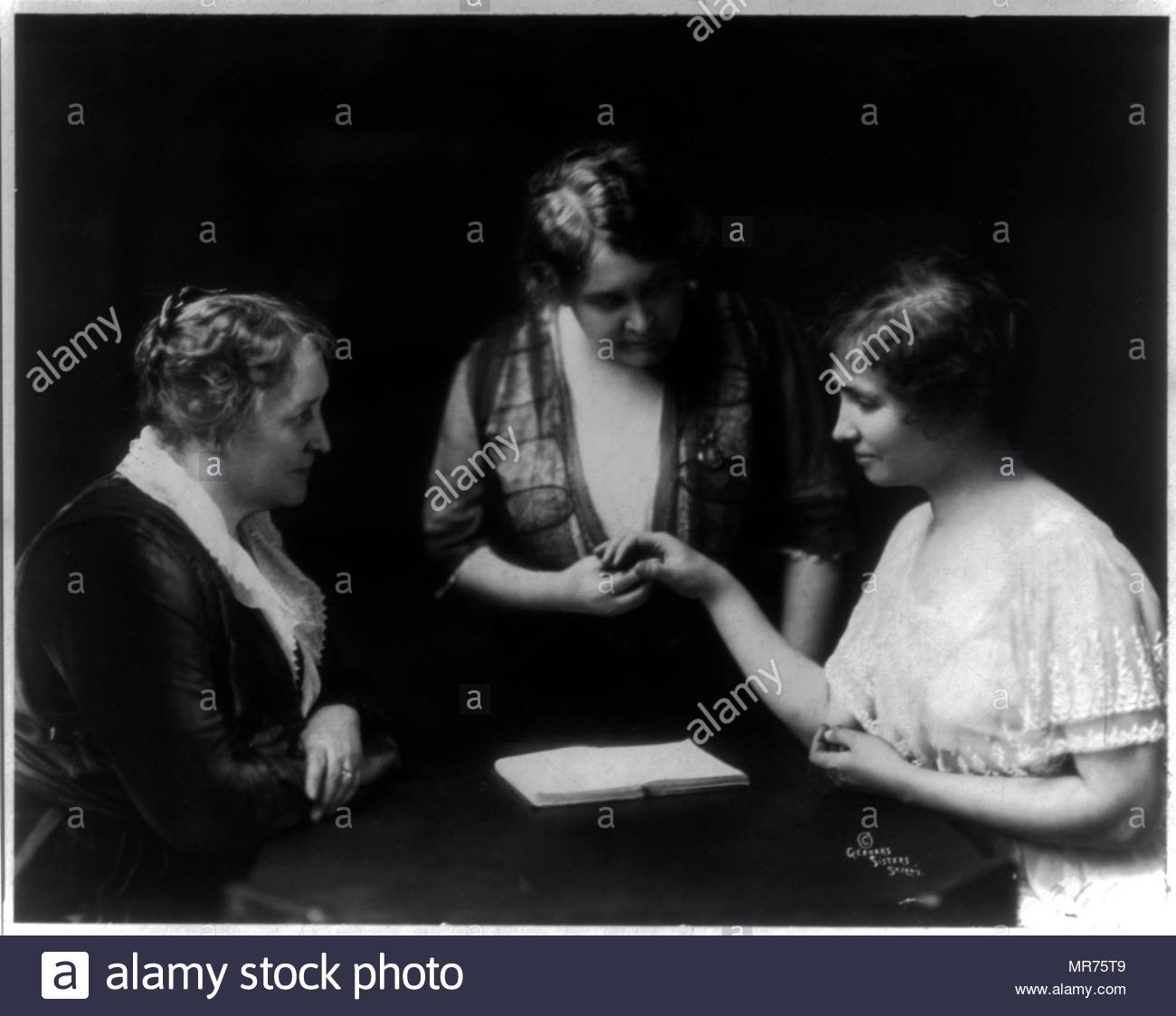 Helen Keller reading a woman's fingers as another woman watches1914  Helen Keller (1880 – 1968), American author, political activist, and lecturer. She was the first deaf-blind person to earn a bachelor of arts degree. she campaigned for women's suffrage, labour rights, socialism, antimilitarism, and other similar causes. - Stock Image