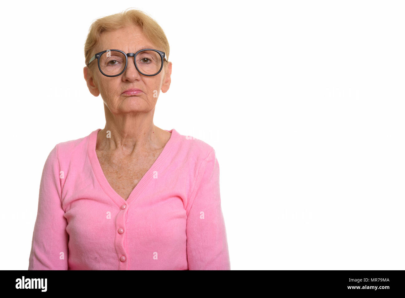 Studio shot of senior nerd woman wearing geeky eyeglasses - Stock Image
