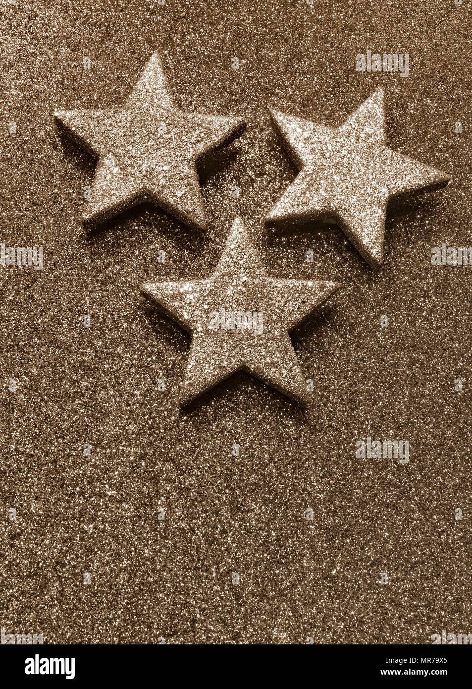 three large silver stars with sepia toned effect - Stock Image