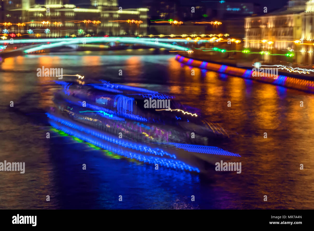 Abstract bright blurred colorful background of night city with ship for travels, excursions with tourists. Neon bright illumination at night on water. - Stock Image