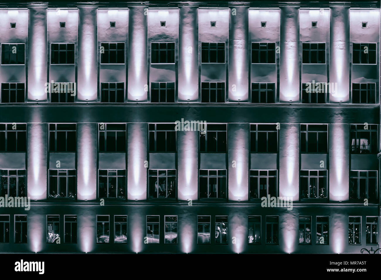 Architectural Background Of Modern Iron Concrete Wall With Windows Skyscrapers Multistory Buildings At Night Illuminated Fasade