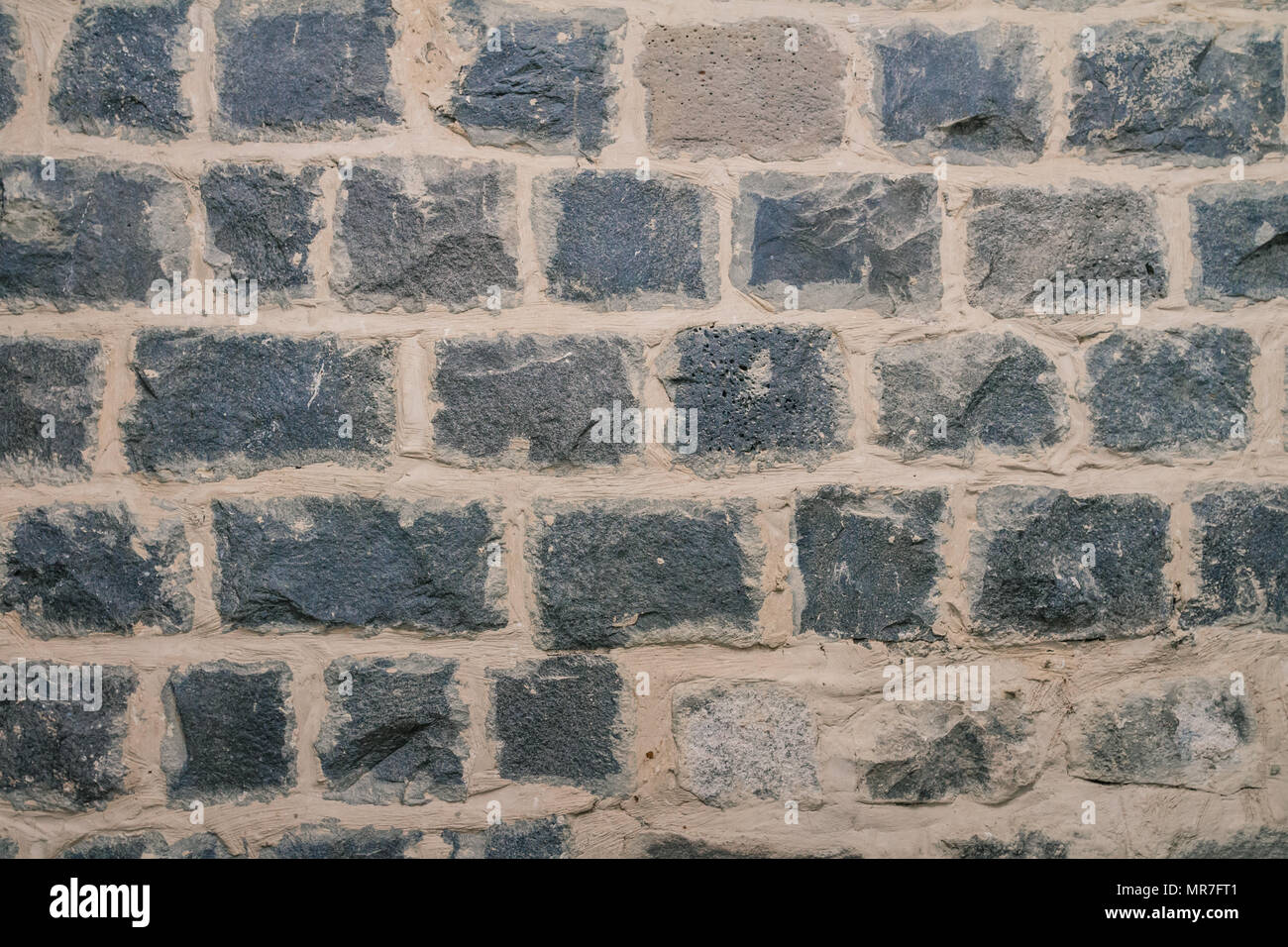 Texture of black basalt brick wall. - Stock Image