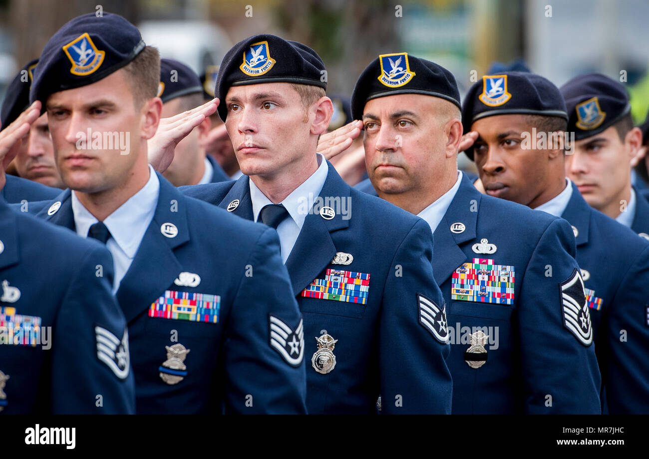 A formation of Security Forces Airmen salutes during the posting of