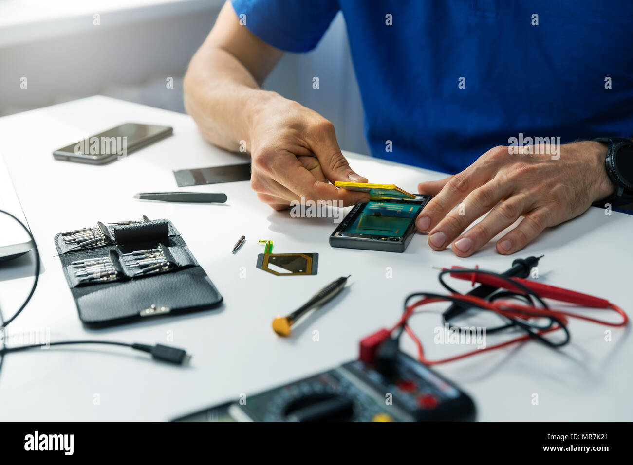 phone maintenance - technician replace the smartphone battery - Stock Image