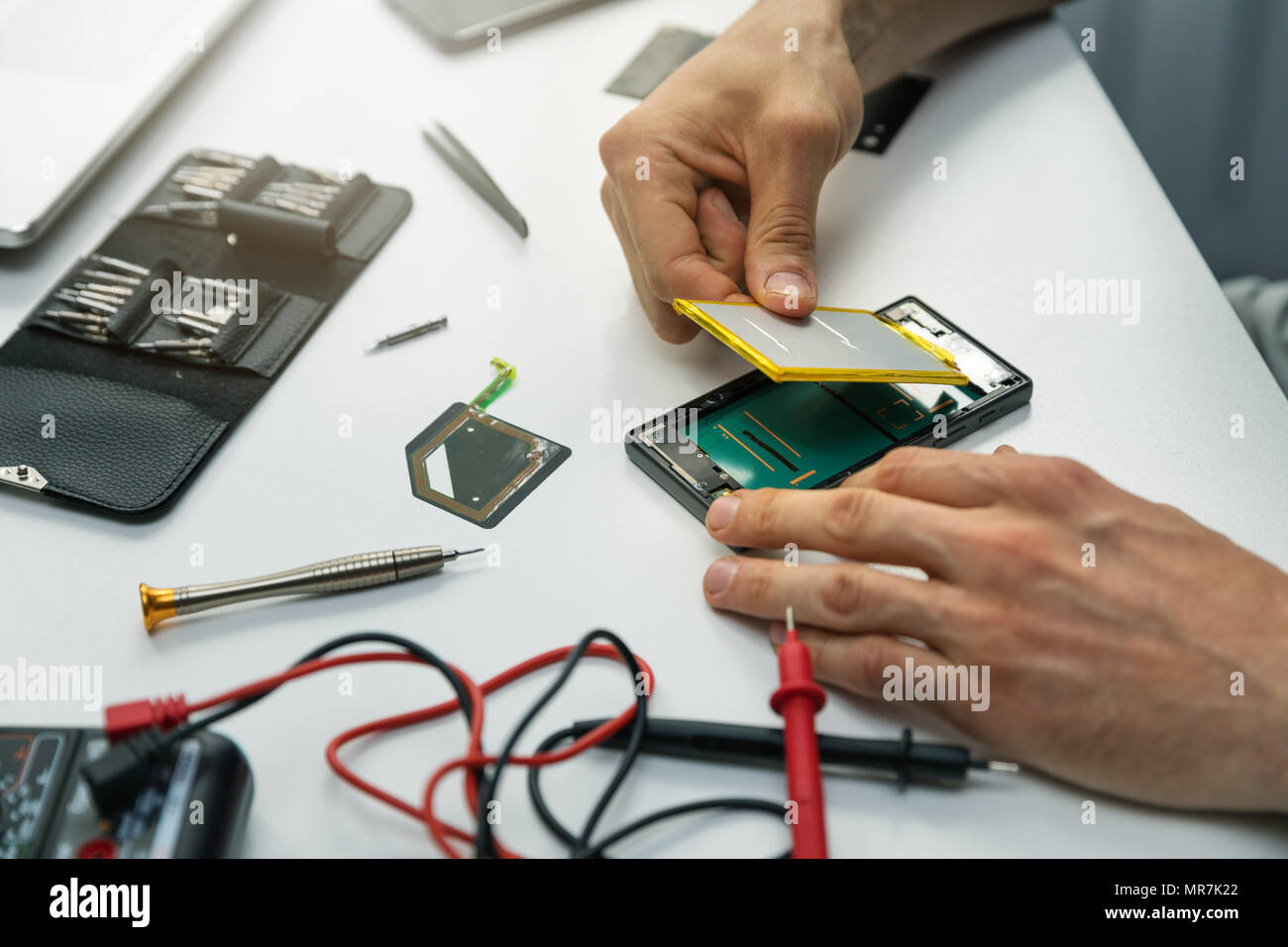technician installing new battery in phone - Stock Image