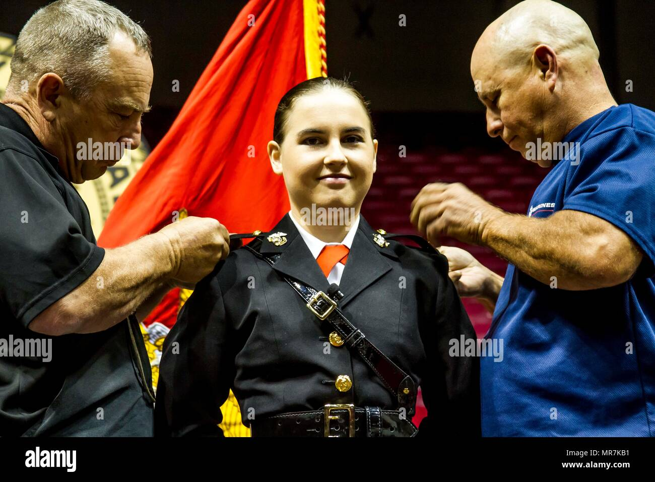 "Mary Sanders gets pinned to the rank of second lieutenant by her father and uncle during her commissioning ceremony at Coleman Coliseum, May 12, 2017. Sanders is a recent graduate of Alabama State University and attended Platoon Leaders Course and Officer Candidate School before being commissioned. ""After a couple of weeks I saw how the Marine Corps worked and was hooked. I was so inspired and motivated that if I had any doubts before, they were gone. This was something I wanted to be a part of."" (U.S. Marine Corps photo by Cpl. Krista James/Released) - Stock Image"