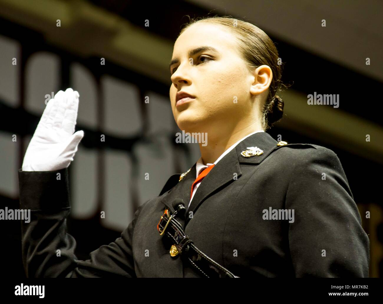 "Mary Sanders raises her hand and takes the Oath of Office in order to become a second lieutenant in the United States Marine Corps during her commissioning ceremony at Coleman Coliseum, May 12, 2017. Sanders is a recent graduate of Alabama State University and attended Platoon Leaders Course and Officer Candidate School before being commissioned. ""After a couple of weeks I saw how the Marine Corps worked and was hooked. I was so inspired and motivated that if I had any doubts before, they were gone. This was something I wanted to be a part of."" (U.S. Marine Corps photo by Cpl. Krista James/Rel - Stock Image"