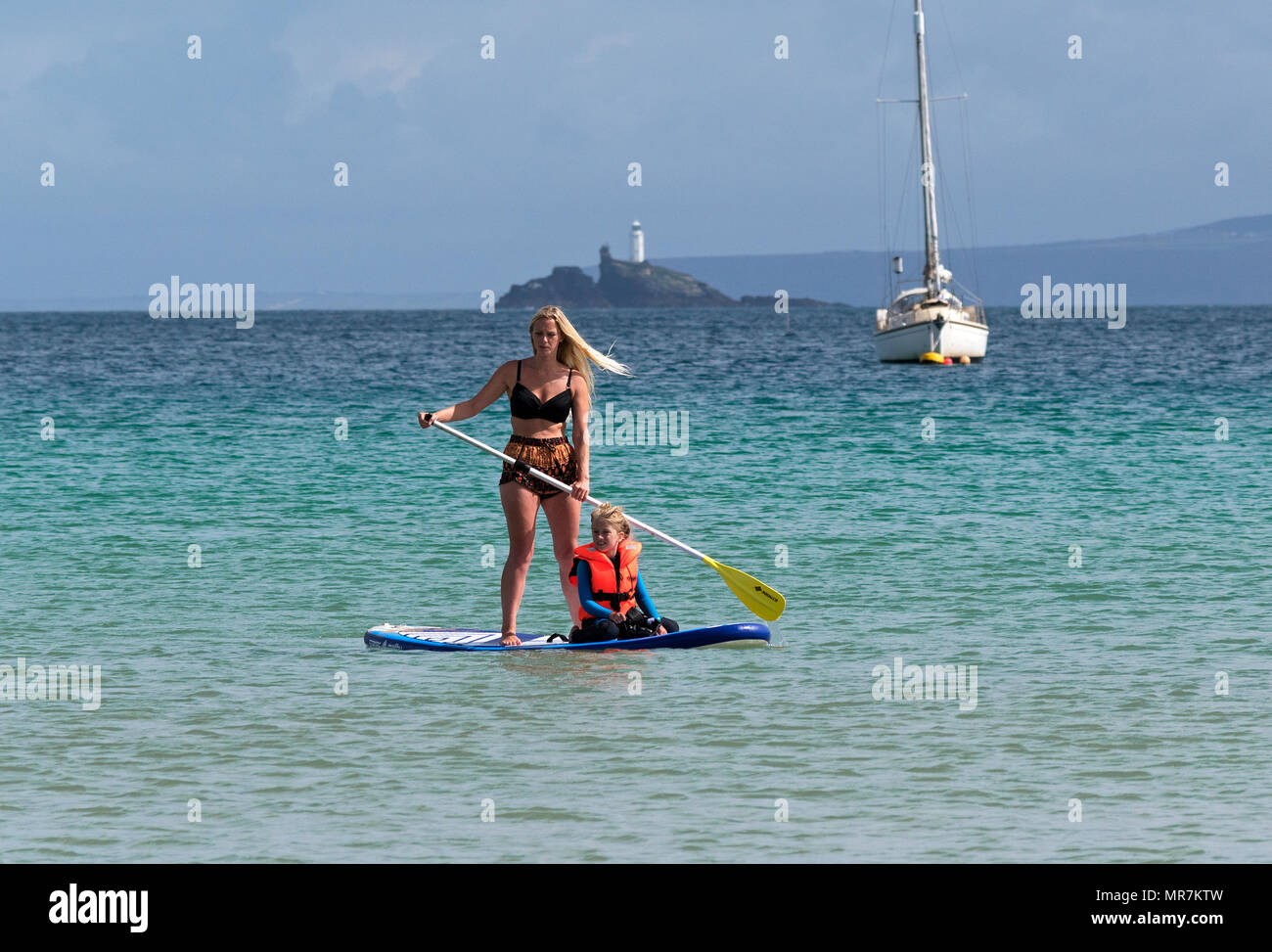 mother and daughter paddleboarding paddle boarding in st.ives bay, cornwall, england, britain, uk. - Stock Image