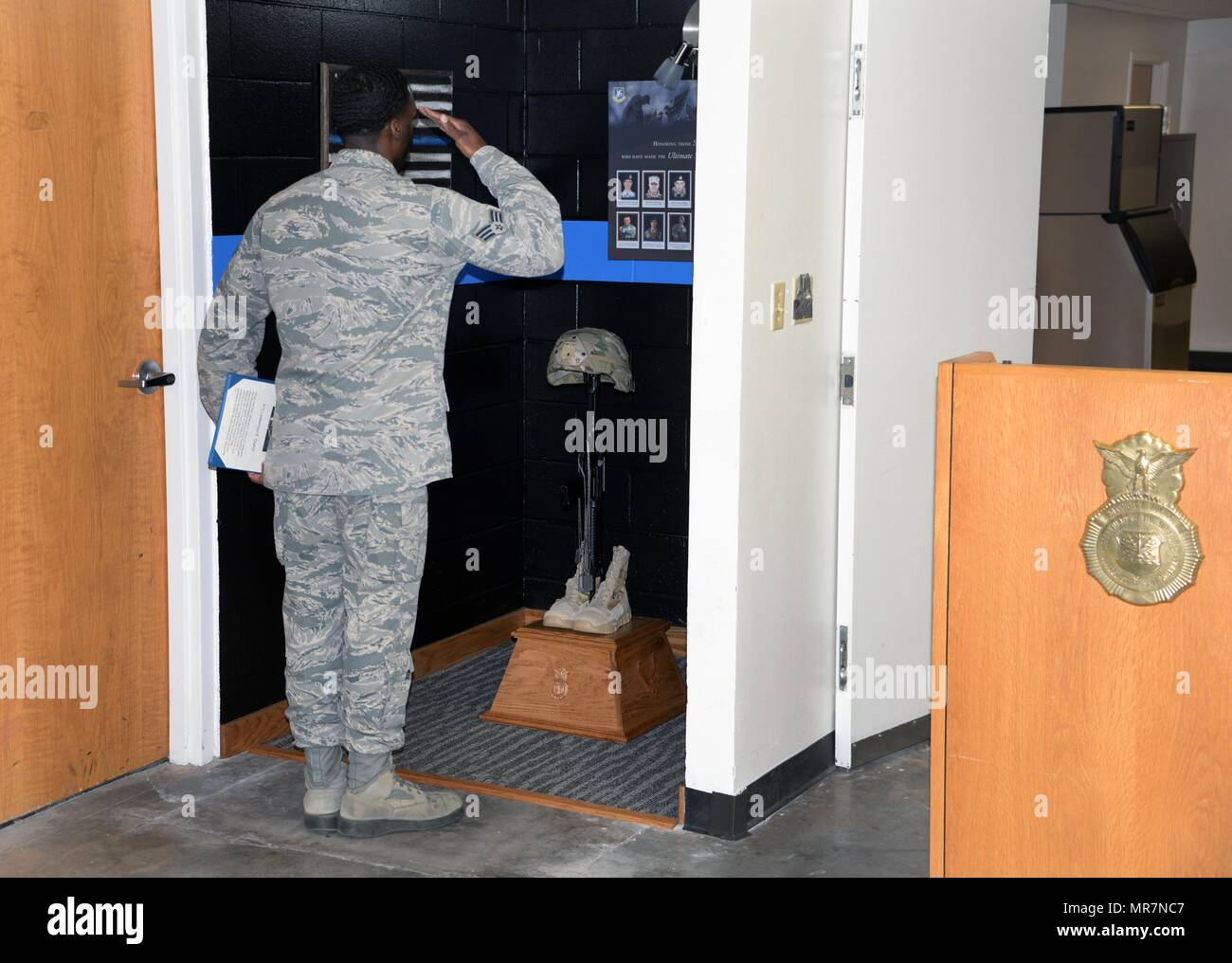 The 82nd Security Forces Squadron held a ceremony at Sheppard Air Force Base, Texas, May 17, 2017, which honored defenders who have made the ultimate sacrifice serving their country. Senior Airman Earnest Jackson Jr., 82nd SFS combat arms instructor, salutes the battlefield cross, which holds the dog tags of fallen defenders. (U.S. Air Force photo by Senior Airman Robert L. McIlrath) - Stock Image