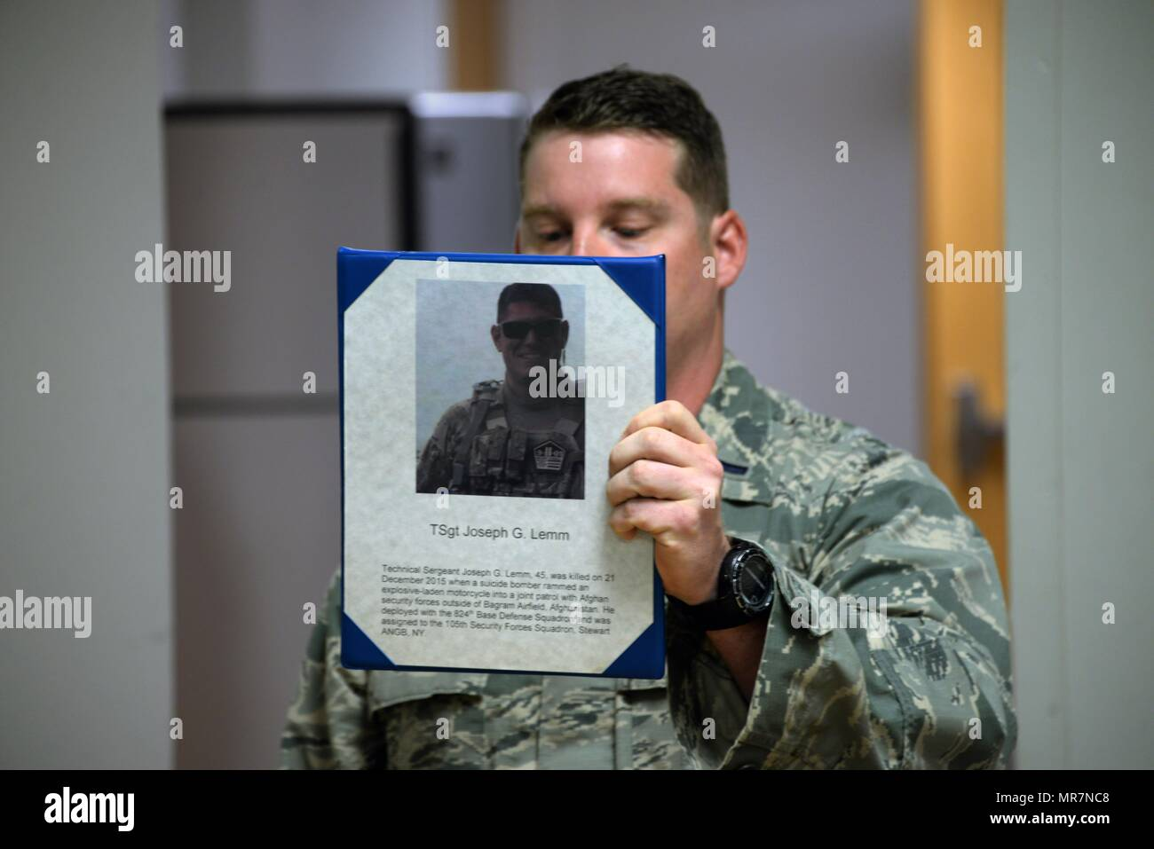 The 82nd Security Forces Squadron held a ceremony at Sheppard Air Force Base, Texas, May 17, 2017, which honored defenders who have made the ultimate sacrifice serving their country. 1st Lt. Bryan Duggan, 82nd SFS operations officer, holds up a picture of Tech. Sgt. Joseph Lemm, a fellow defender who was killed on Dec. 21, 2015, by a suicide bomber. Lemm was assigned to the 105th SFS at Stewart Air National Guard Base, New York. (U.S. Air Force photo by Senior Airman Robert L. McIlrath) - Stock Image