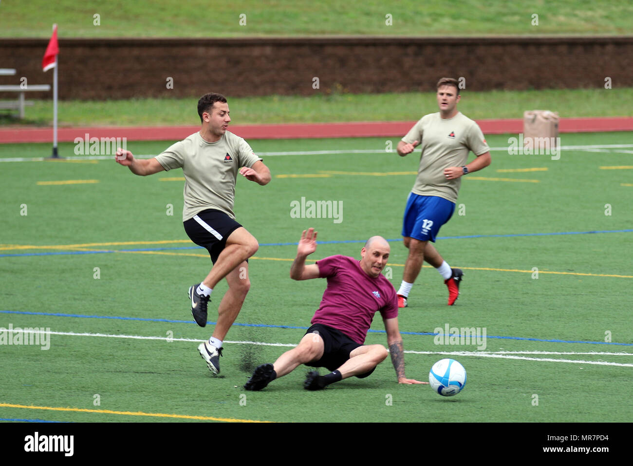 """British Paratroopers assigned to the 3rd (United Kingdom) Division's Signal Regiment and from the 216th Parachute Signal Squadron fight to gain ball possession during an All American Week 100 soccer match at Towle Stadium, Fort Bragg, N.C., May 23, 2017. During All American Week 100, Paratroopers from throughout the Division competed in softball, soccer, flag football, tug-of-war, combatives, boxing, a best squad competition, a combat fitness test and the Little Group of Paratroopers competition for bragging rights and a shot at """"Best Battalion."""" All American Week is an opportunity for Paratro - Stock Image"""
