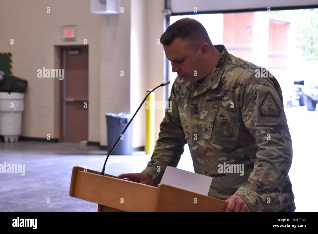 U.S. Army National Guard soldier Master Sgt. Jason Williamson of Bravo Company, Recruiting and Retention Command, reads a script for a graduation ceremony in the Queensbury Armory, Queensbury, N.Y., May 21, 2017. Williamson was preparing for a graduation/Battle Handoff ceremony. (U.S. Army National Guard photo by Pfc. Andrew Valenza) - Stock Image