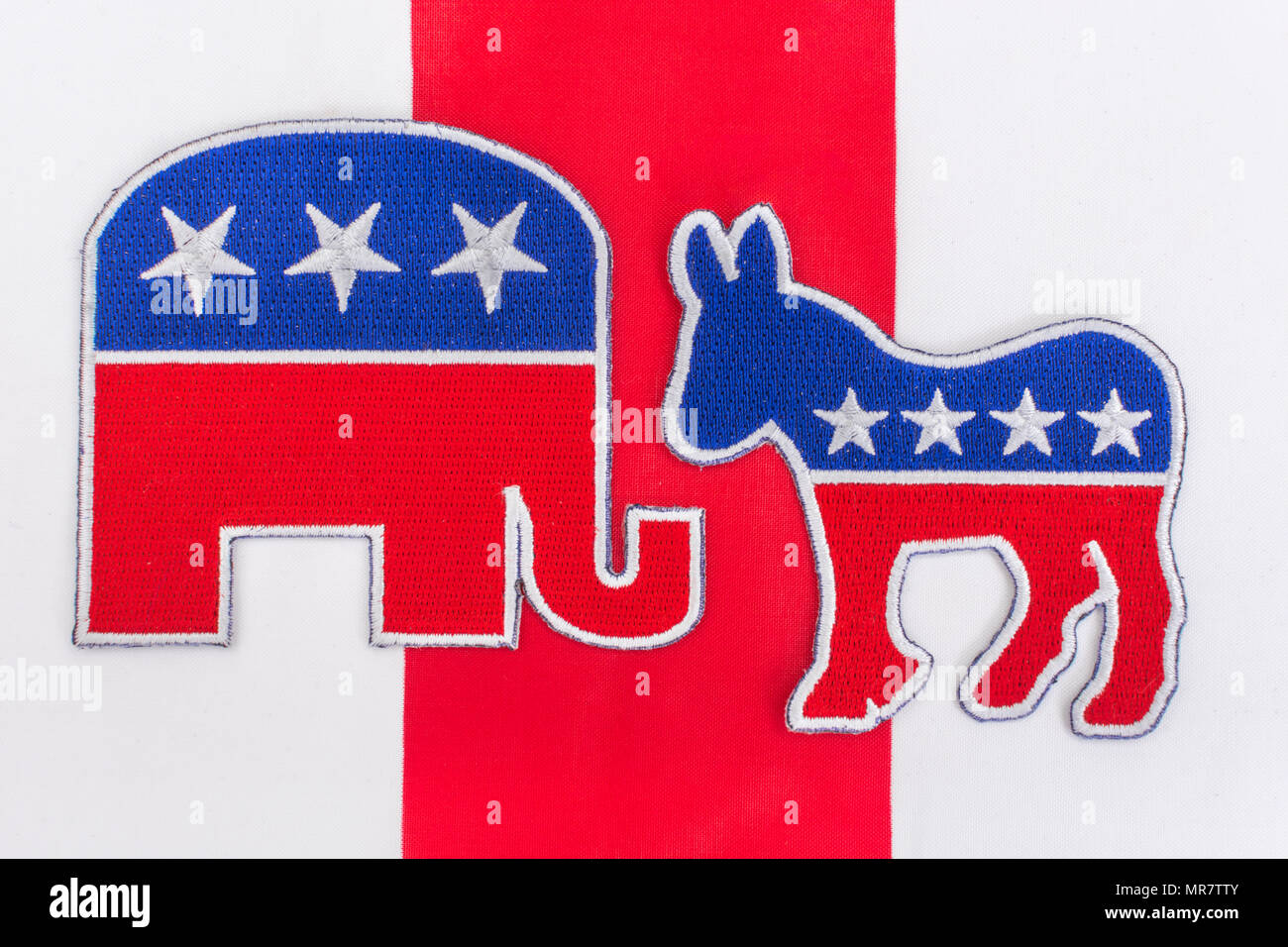 US Democrat Donkey logo & Republican elephant logo on Stars and Stripes - metaphor for 2018 US Midterm election, Midterms, and Presidential elections. - Stock Image