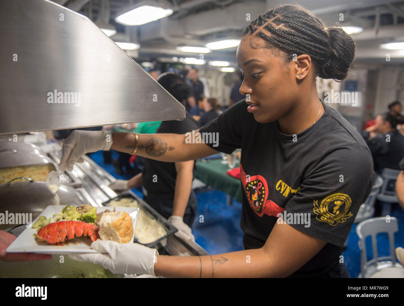 170520-N-FE442-035 ARABIAN GULF (May 20, 2017) Machinist's Mate 3rd Class Khiarea Deshazer prepares a plate for the Mother's Day dinner aboard the aircraft carrier USS George H.W. Bush (CVN 77) (GHWB). GHWB is deployed in the U.S. 5th Fleet area of operations in support of maritime security operations designed to reassure allies and partners, and preserve the freedom of navigation and the free flow of commerce in the region. (U.S. Navy photo by Mass Communication Specialist 3rd Class Matt Matlage/Released) - Stock Image