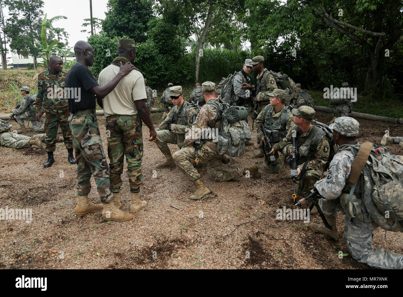 U.S. Soldiers assigned to the 1st Battalion, 506th Infantry Regiment, 1st Brigade Combat Team, 101st Airborne Infantry Division receive instructions from the Ghana Armed Forces during United Accord 2017 at the Jungle Warfare School on Achiase military base in Akim Oda, Ghana on May 20, 2017. The Jungle Warfare School is a series of situational training exercises designed to train participants in counter-insurgency and internal security operations. (U.S. Army photo by Pfc. Joseph Friend) - Stock Image