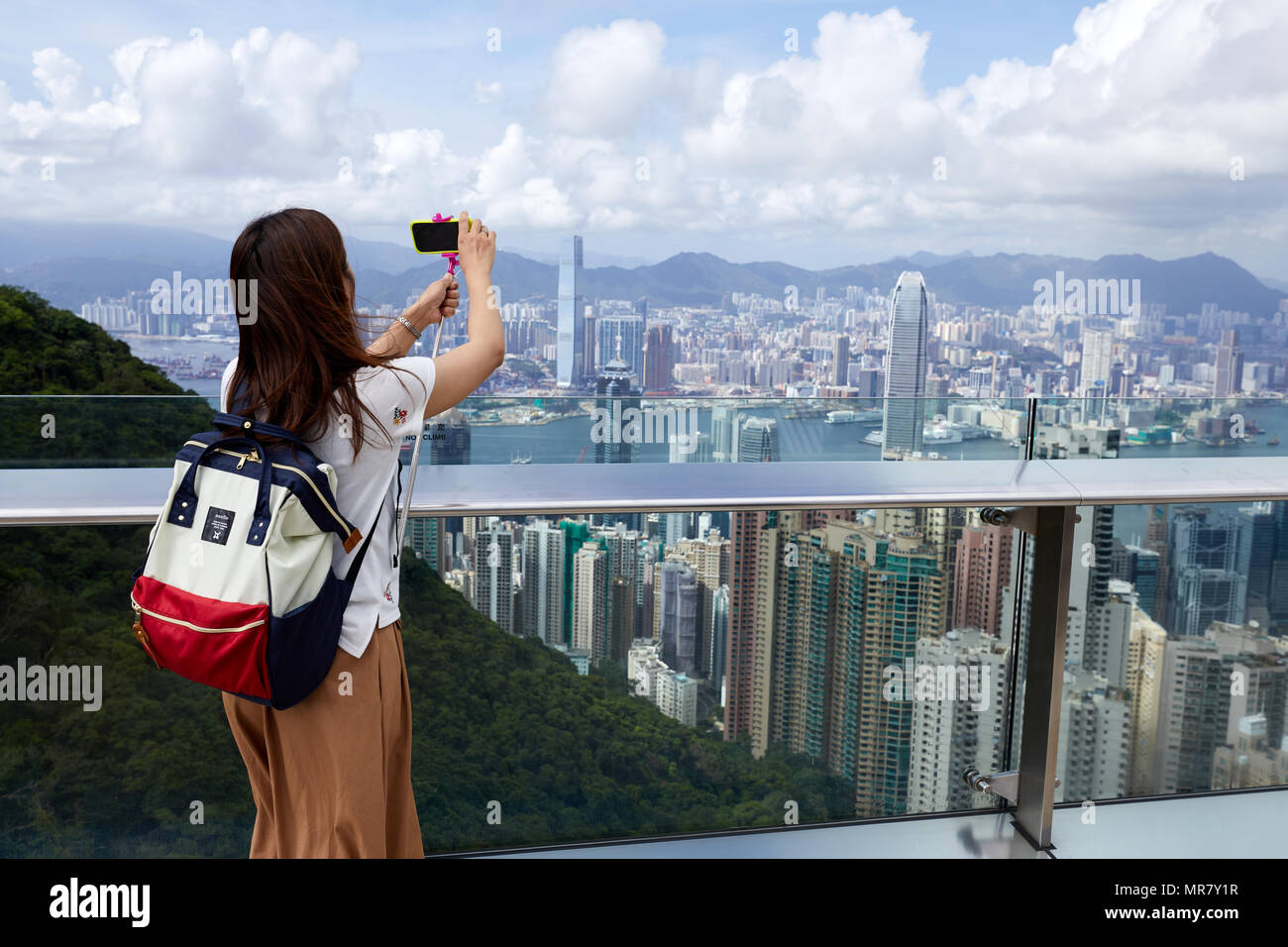 A sightseer takes photos of Hong Kong, looking towards Kowloon, as viewed from Victoria Peak on Hong Kong Island and overlooking the city. - Stock Image