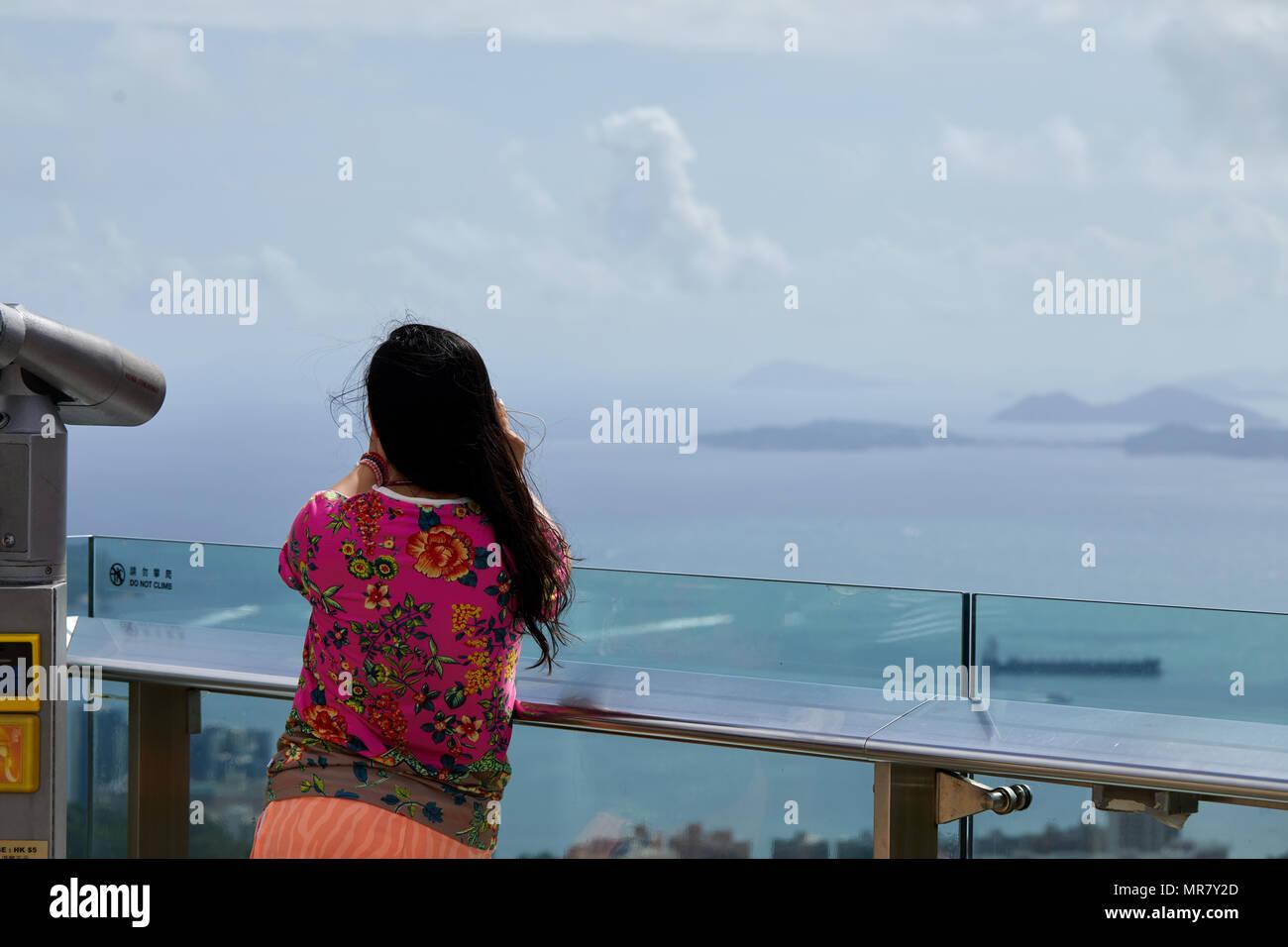 A sightseer looking towards Lamma Island, Hong Kong, viewed from Victoria Peak on Hong Kong Island and overlooking the city. - Stock Image