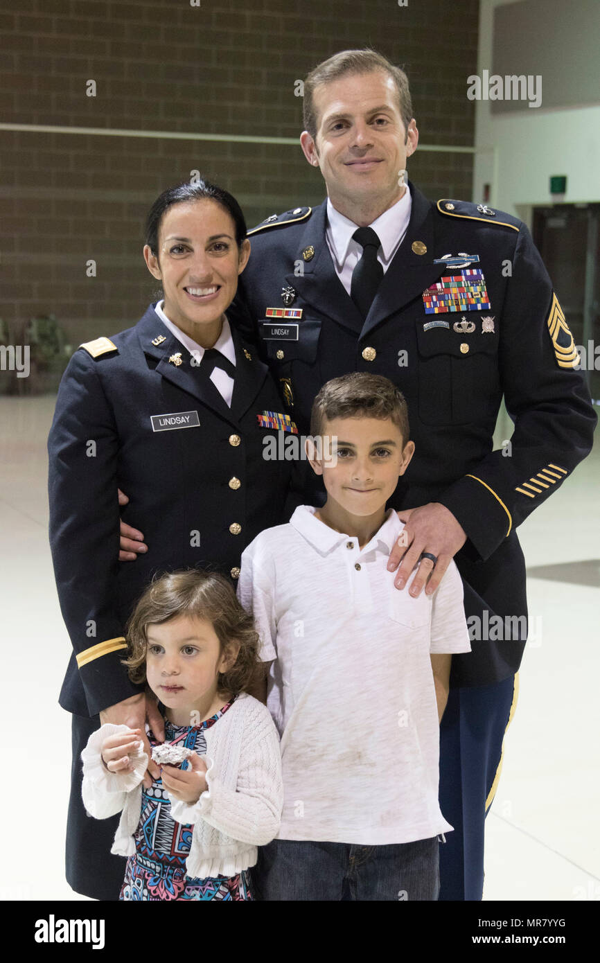 2nd Lt. Marisa Lindsay poses with her husband, Master Sgt. Michael Lindsay, Special Forces Advisor with the 1-196th Infantry Regiment, son Liam, 10, and daughter Esmarin, 4, after a commissioning ceremony at the National Guard armory on Joint Base Elmendorf-Richardson, Alaska, May 21, 2017. Lindsay earned the distinction of Honor Graduate and was recognized with the High Physical Fitness Award from the Officer Candidate School at the Alabama Military Academy.    (U.S. Army National Guard photo by Spc. Michael Risinger) - Stock Image