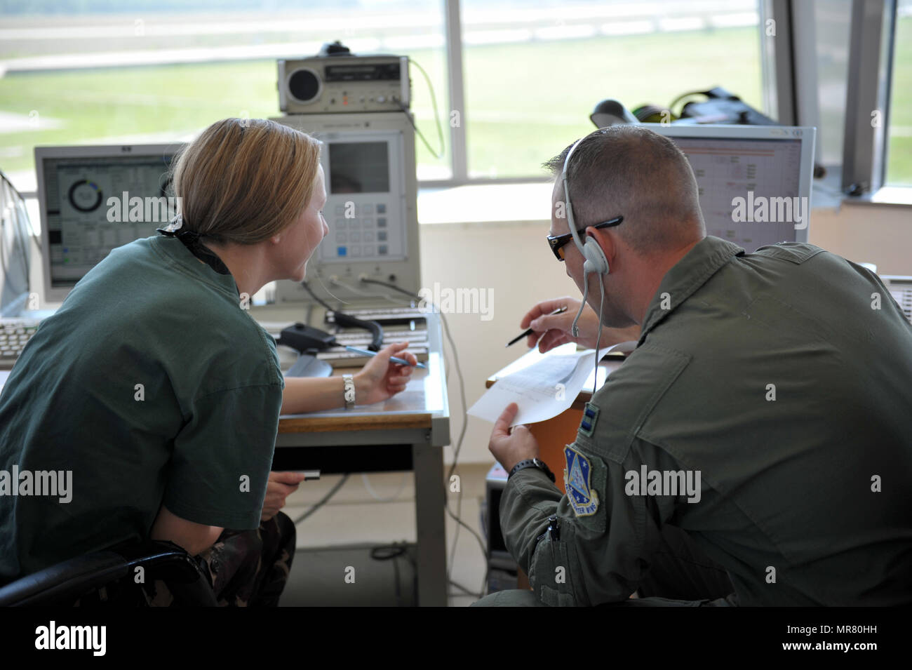 Capt. Justin Kreischer, an F-16 pilot assigned to the 180th Fighter Wing, Ohio Air National Guard works alongside 1Lt. Krisztina Kovacs, a ground controller assigned to the Hungarian Air Force, while in the air traffic control tower May 26, 2017 at Kecskemet Air Base, Hungary. Approximately 150 Airmen and eight F-16 fighter jets from the 180FW traveled to the air base to participate in Load Diffuser 17, a two-week Hungarian-led multinational exercise focused on enhancing interoperability capabilities and skills among NATO allied and European partner air forces by conducting joint operations an - Stock Image