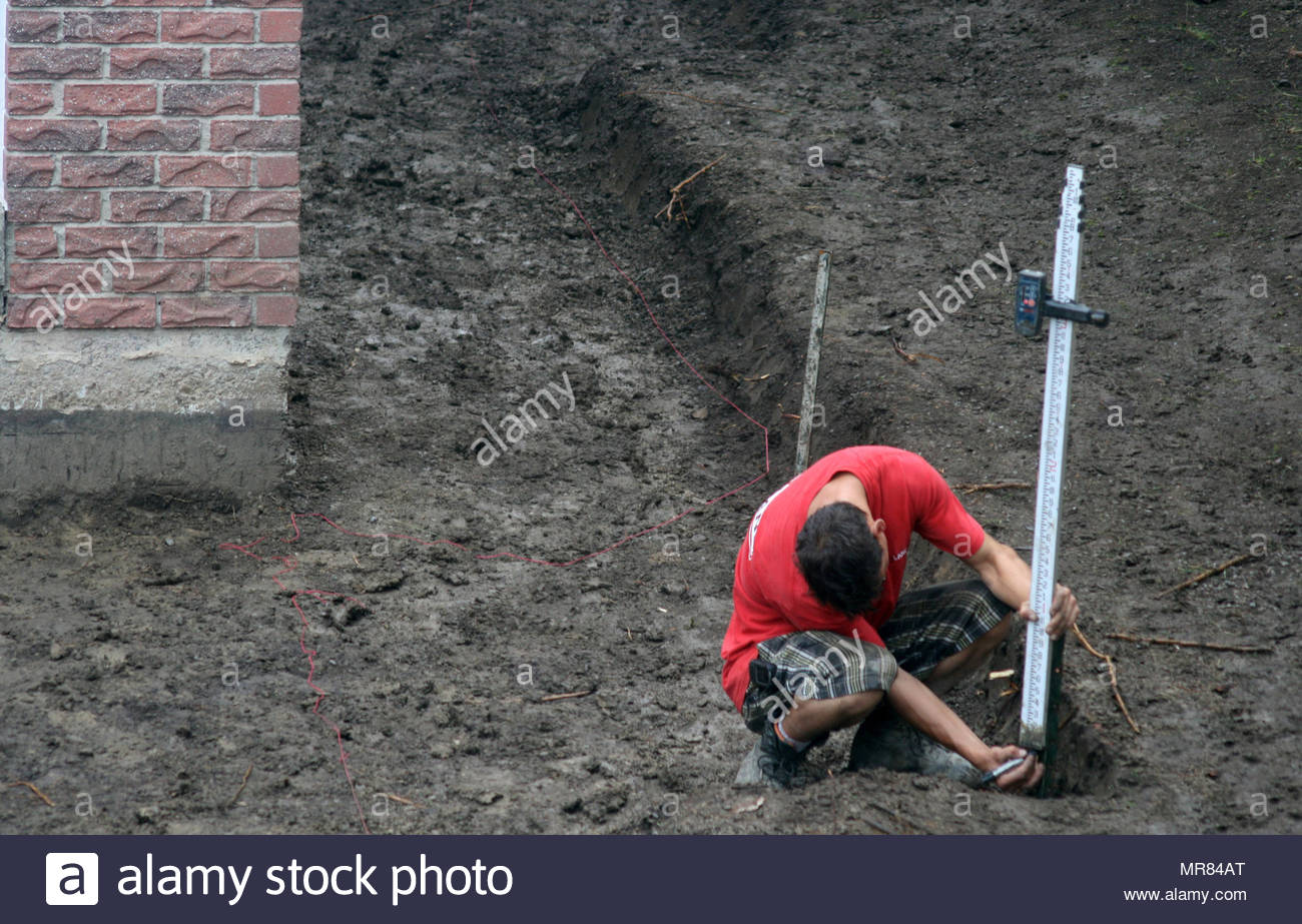 A landscaper uses a measuring stick to mark out an area in a backyard before installing interlocking patio stones. - Stock Image