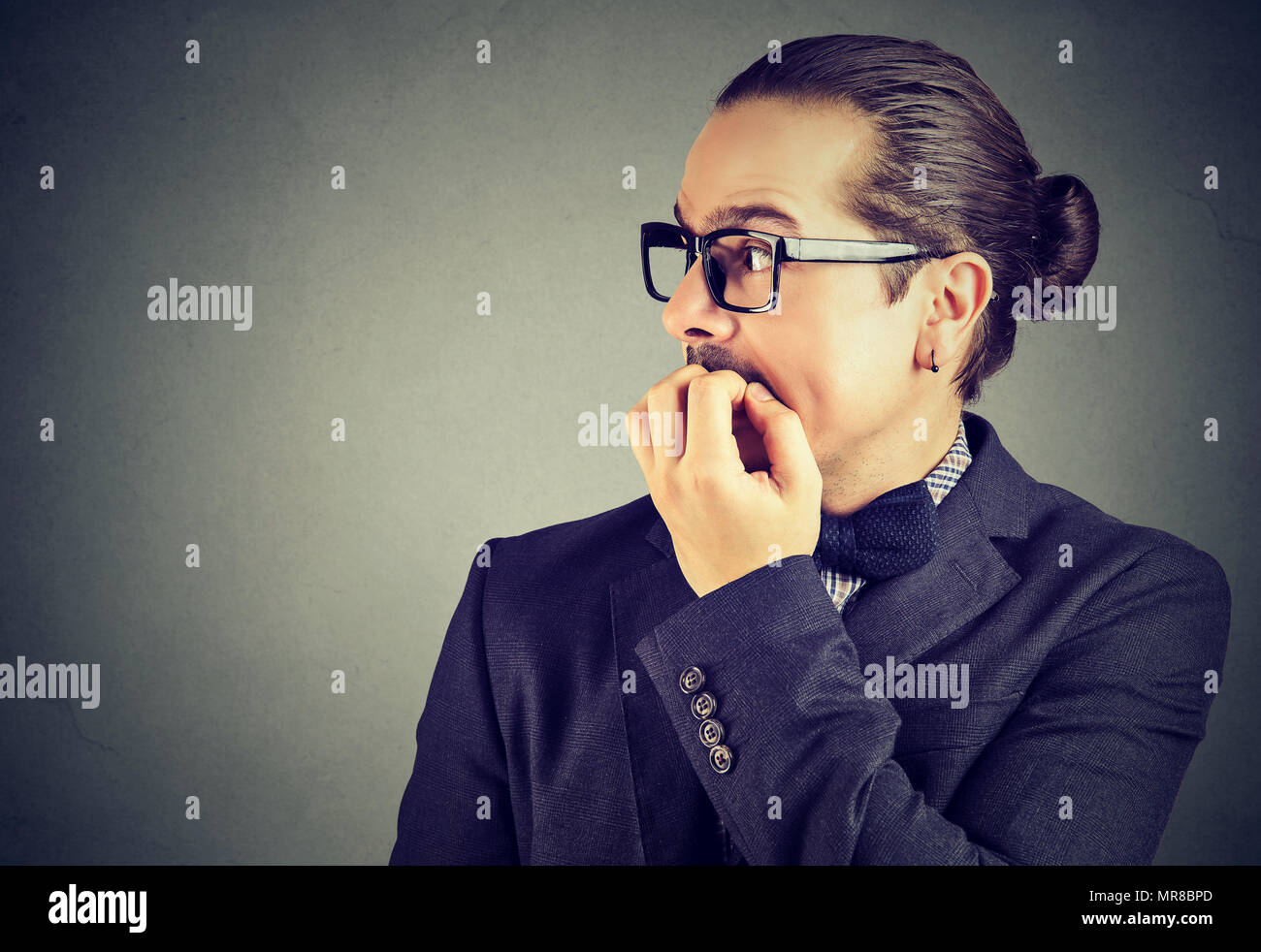 Preoccupied anxious young man biting his fingernails looking to the side - Stock Image