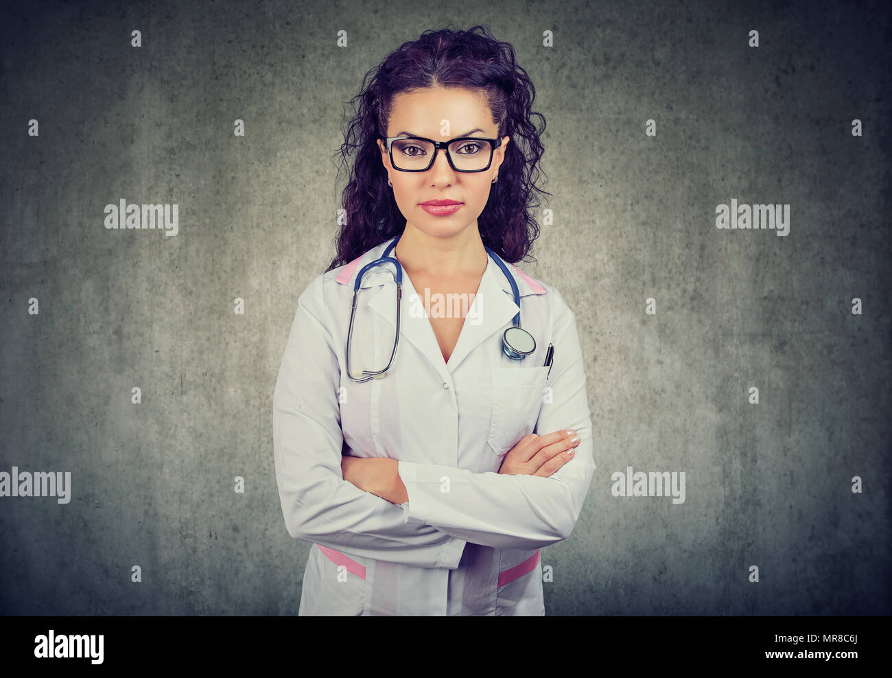 Beautiful woman in glasses wearing white apparel of doctor and stethoscope looking confidently at camera. - Stock Image